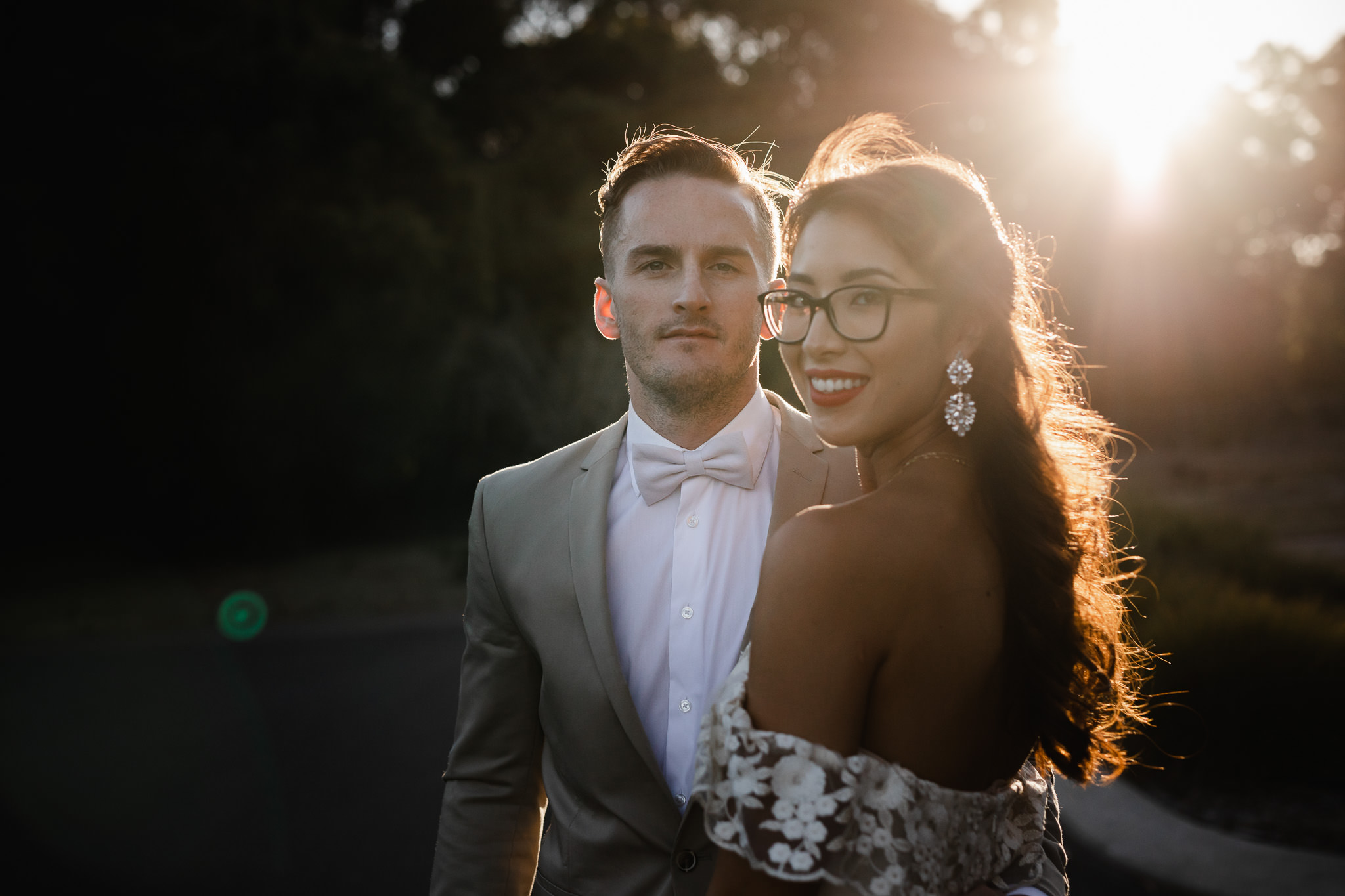 Bride with glasses and groom with bow tie looking at the camera while standing in front of dark trees and bright sun flare over their shoulder