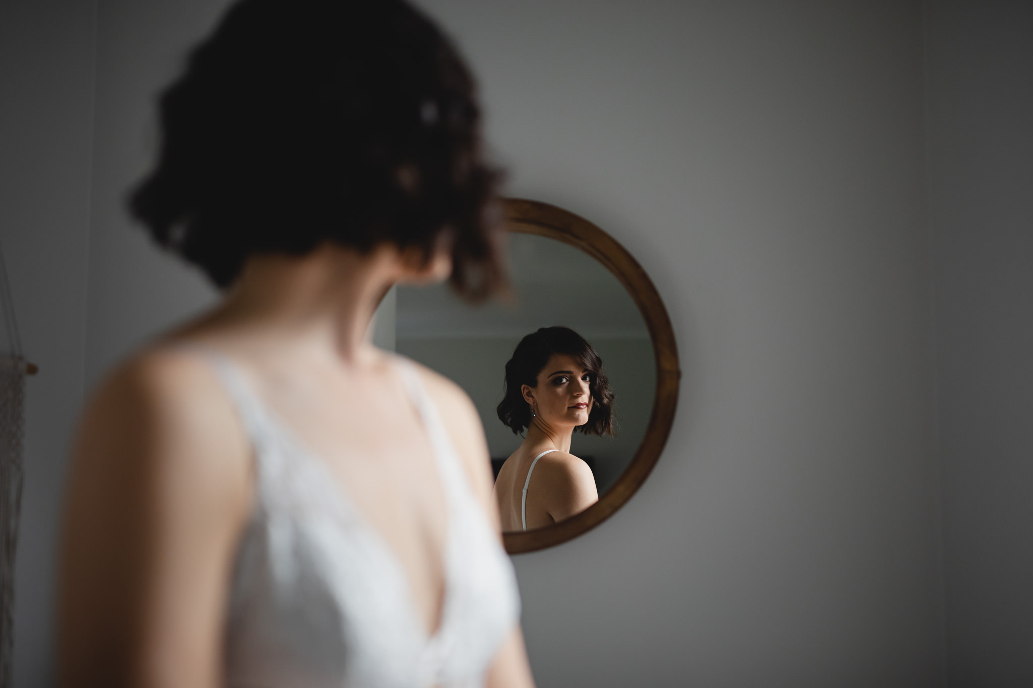 Vintage style bride looking over her shoulder at reflection of herself in mirror