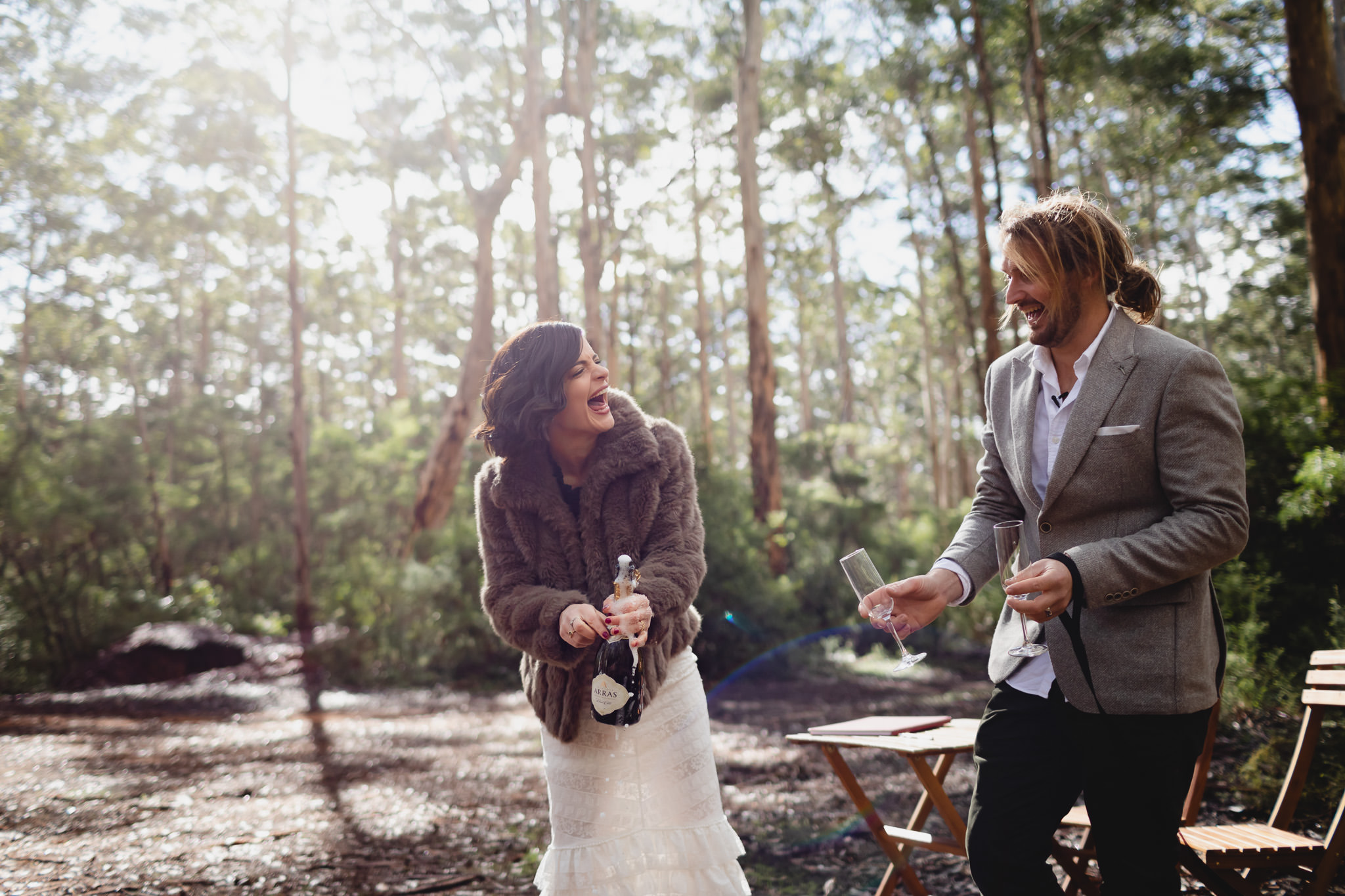 Bride with vintage fur coat laughing with groom while opening a bottle of champagne in Boranup forest at their winter wedding