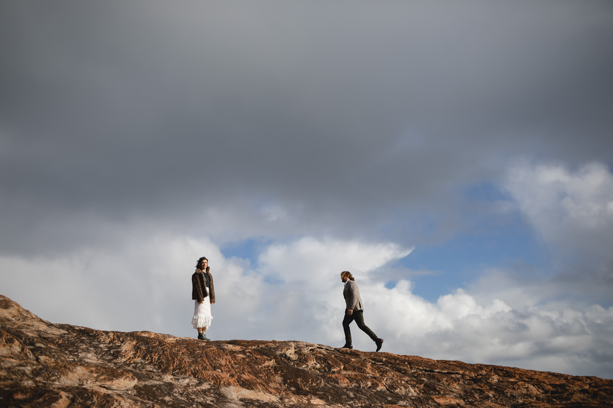 Bride and groom walking along red rocks at Redgate Beach in Margaret River at their winter elopement wedding