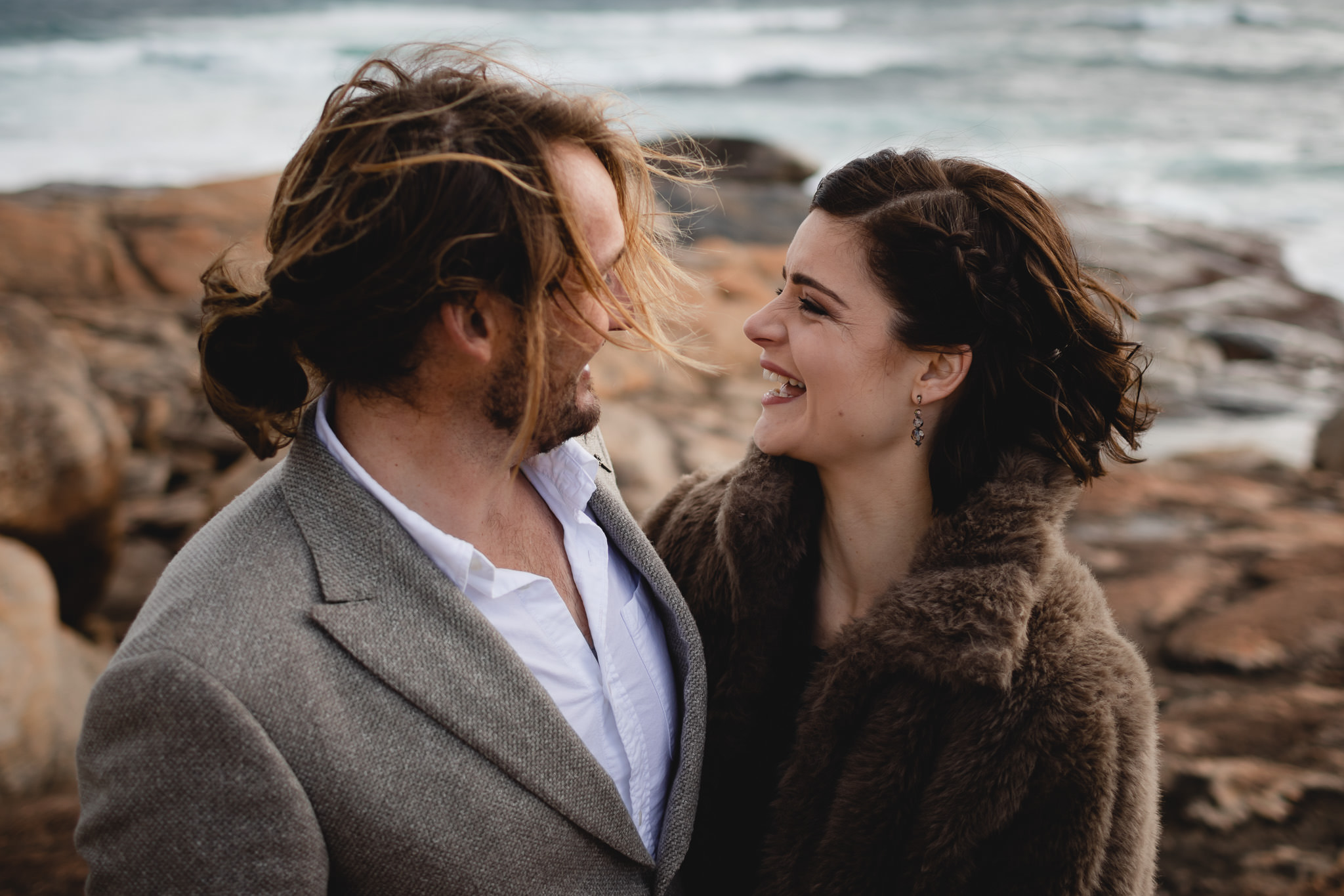 Vintage style bride and groom laughing with windswept hair on stormy winter wedding at Redgate Beach near Margaret River
