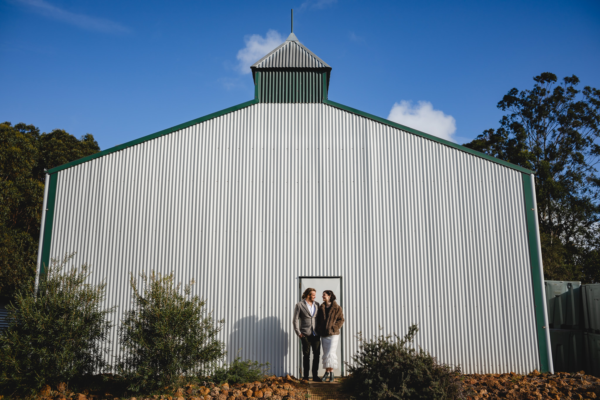 Wedding photo of bride and groom in front of barn style winery building at their Hay Shed Hill wedding