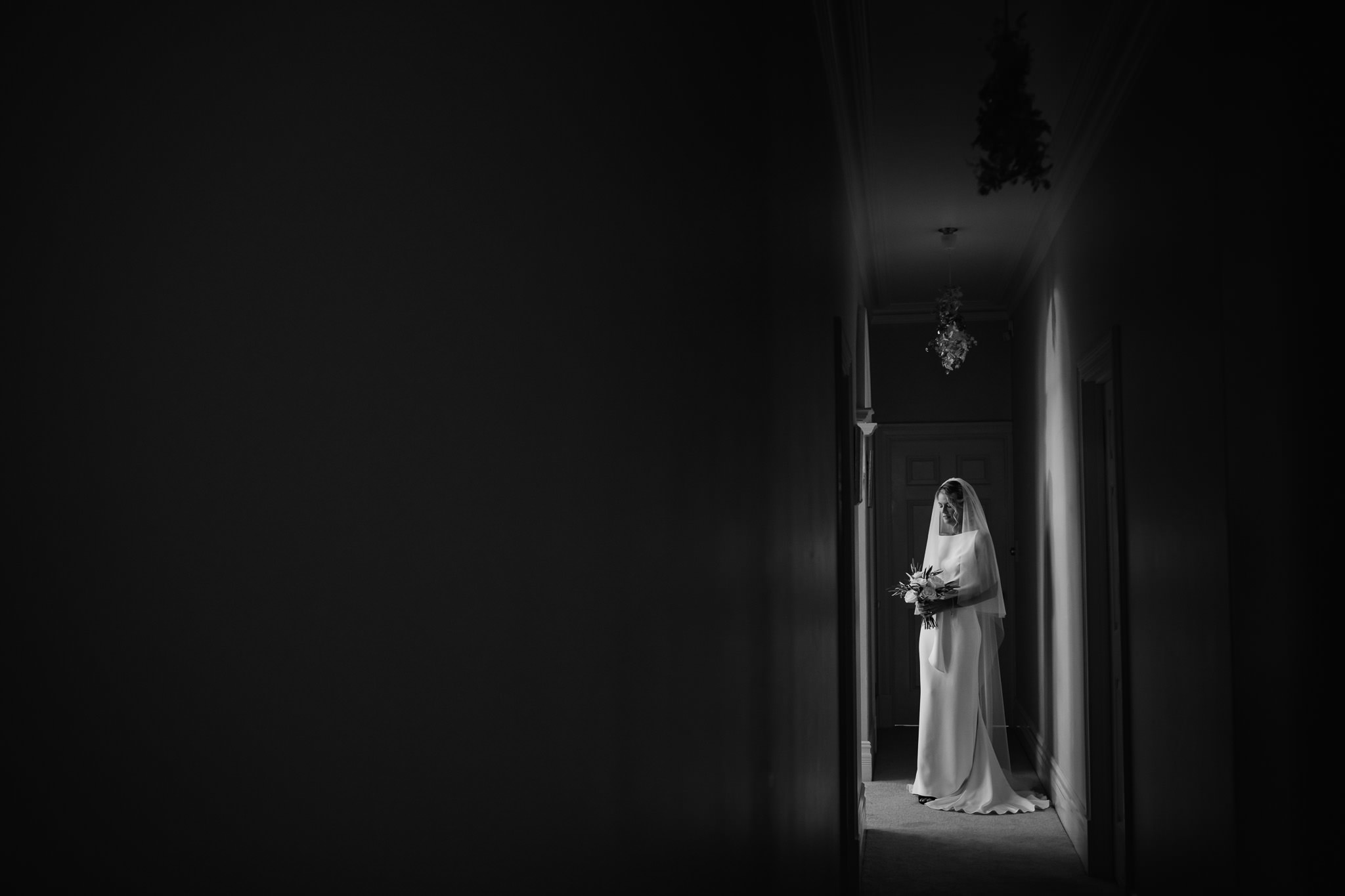 Black and white portrait of bride in Lola Varma wedding dress standing in the hallway of her parent's house before her backyard wedding in Dalkeith