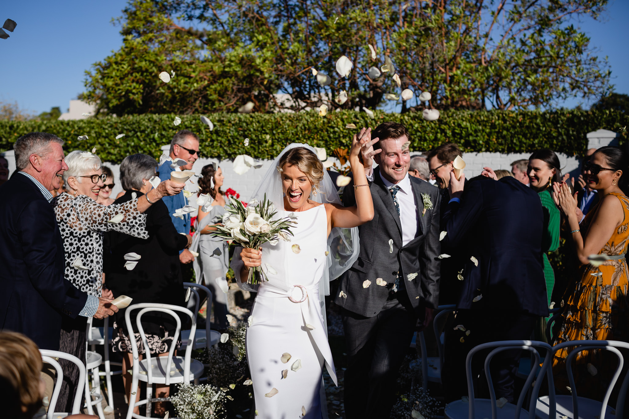 Bride and groom laughing and smiling as guests throw white flower petals at them as they walk back down the aisle of their backyard wedding at her paren't house in Dalkeith, Western Australia