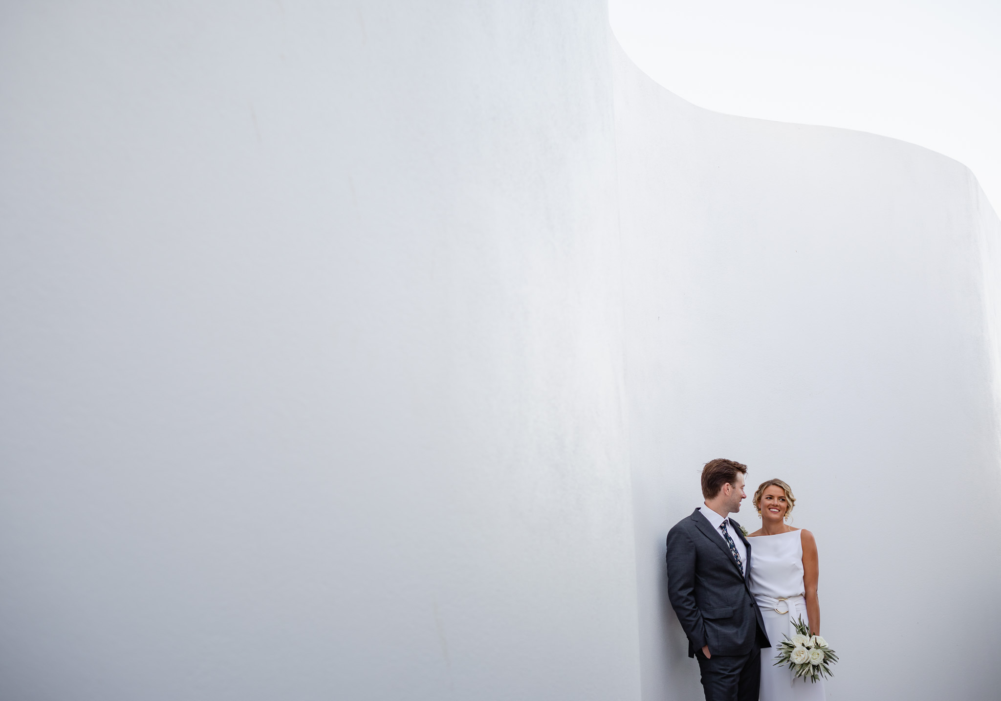 Modern bride and groom leaning against curved white wall on their wedding day