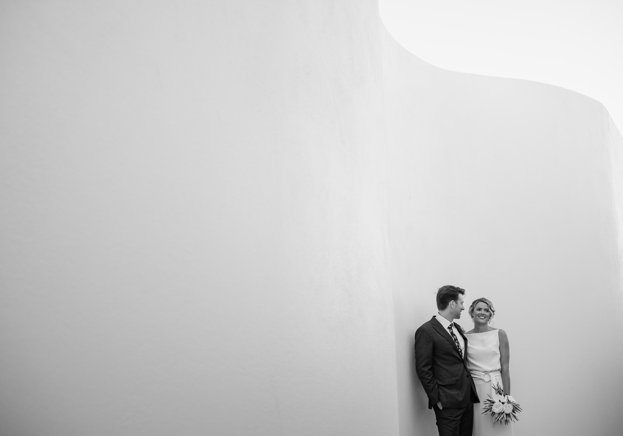 bride and groom leaning against curved wall of modern house