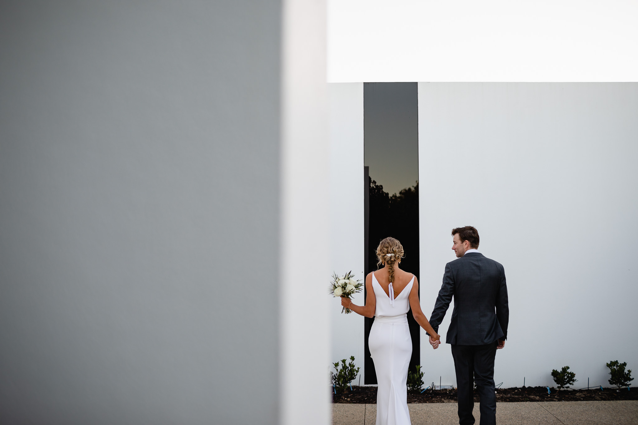 bride and groom outside modern architect designed home with minimalist design