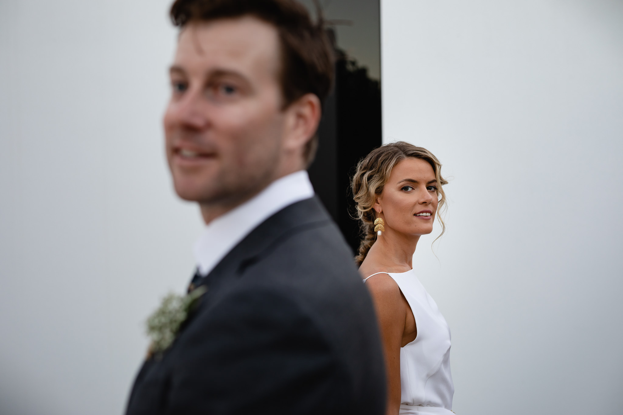 Bride looking over her shoulder past groom in front of black and white lines on a modern building