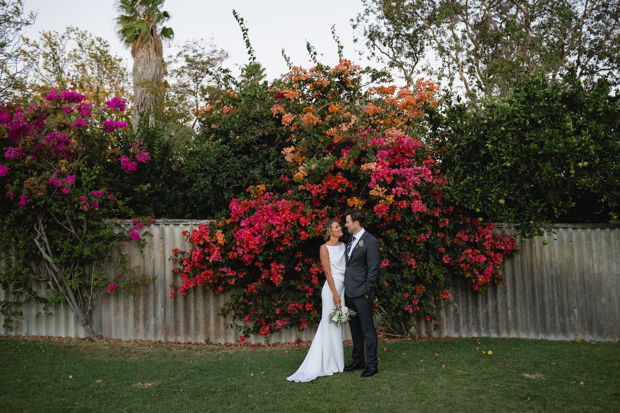Modern bride and groom standing in front of colourful red, pink and purple Bougainvillea on front verge at their backyard wedding in Dalkeith in Western Australia