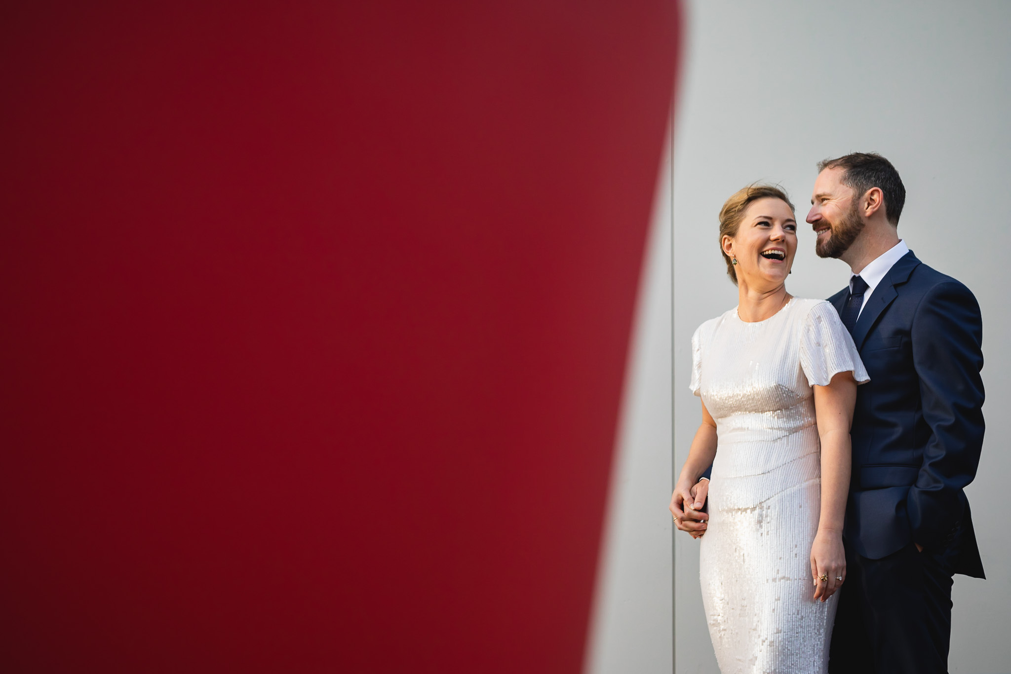 Bride and groom laughing while taking wedding photos on the street in Bunbury with a red and white wall