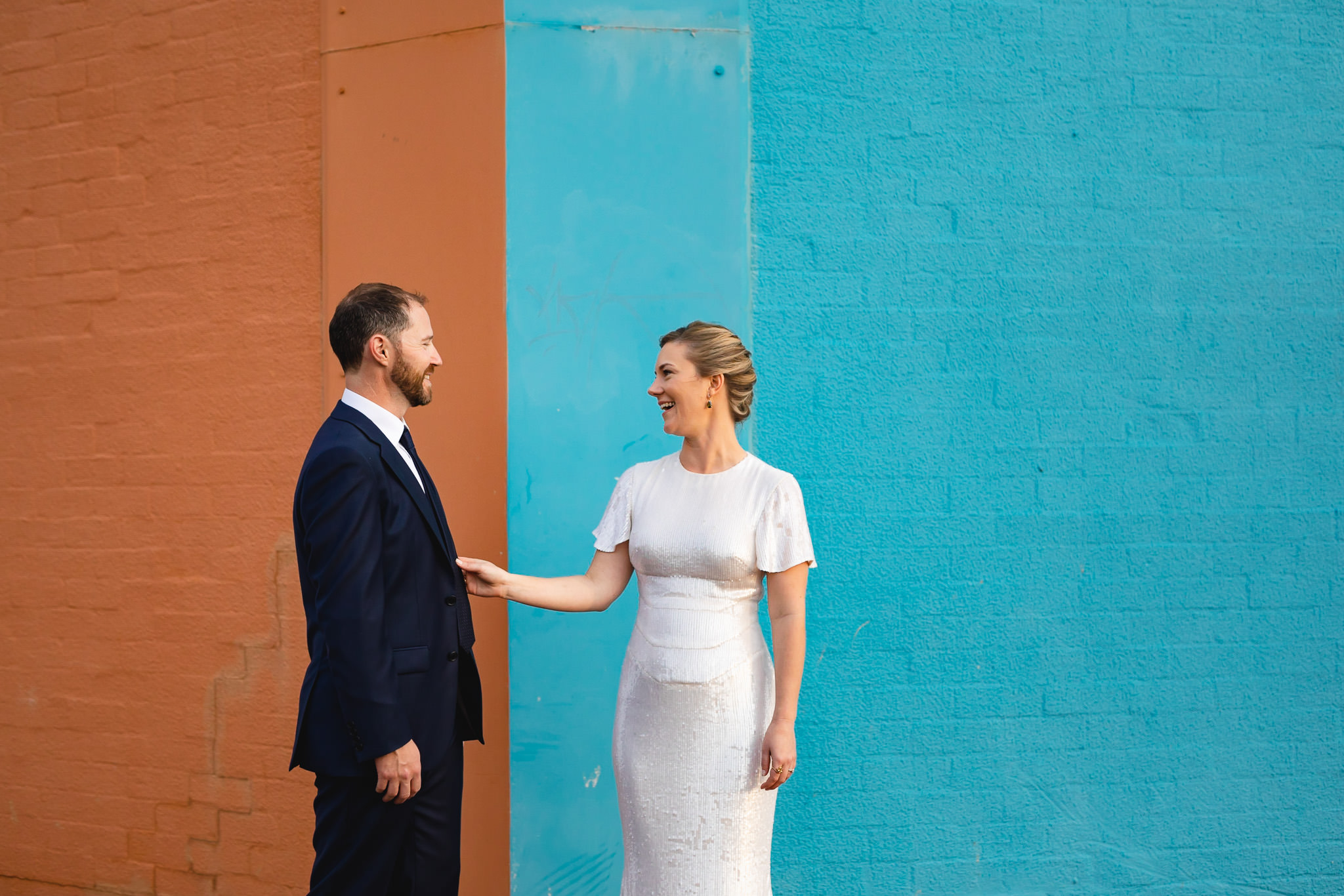 Laughing bride adjusting groom's tie while standing in front of orange and blue wall at The Commercial Club in Bunbury at their wedding at Maker and Co