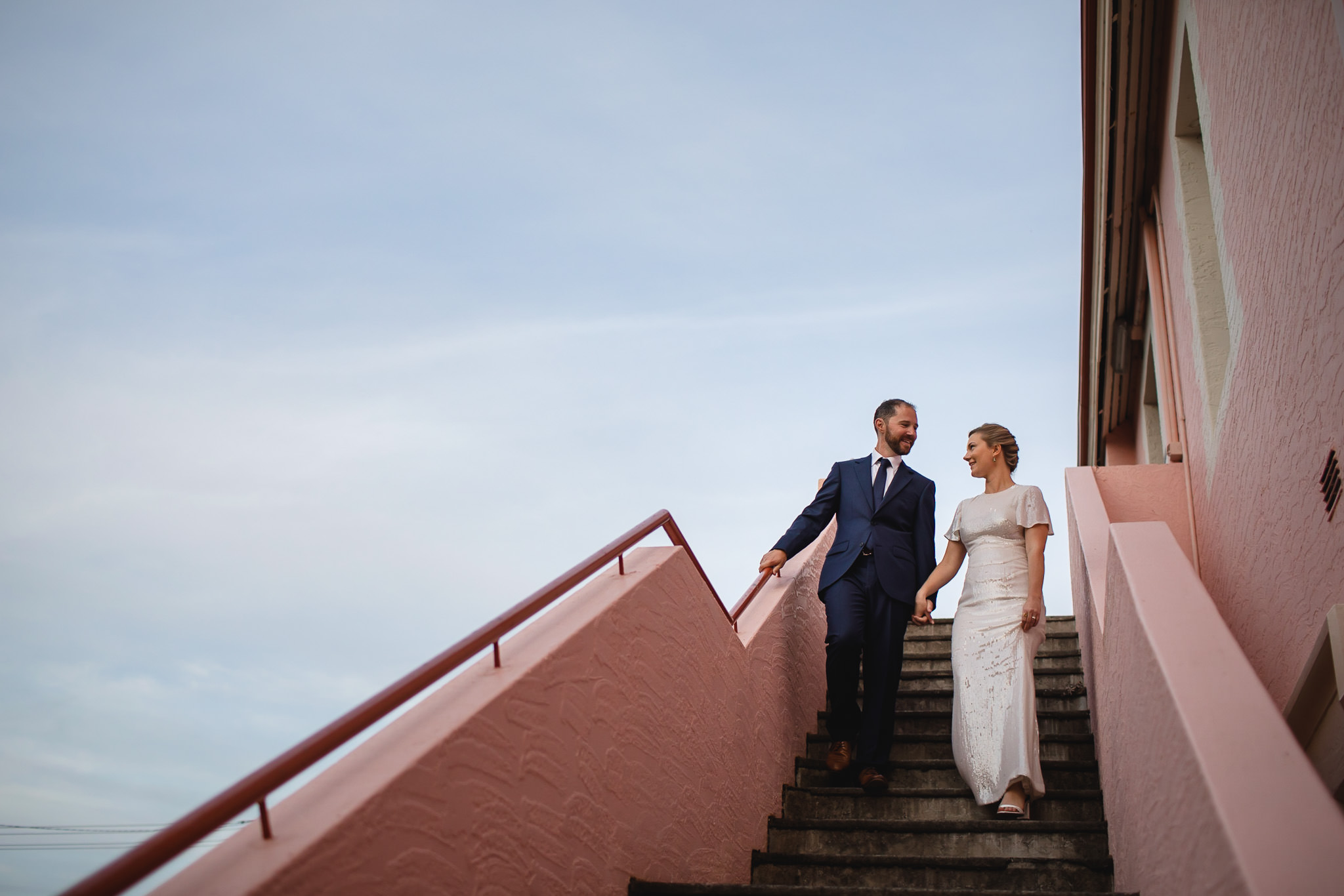 Bride and groom walking down pink staircase at Bunbury Regional Art Gallery with blue sky in background