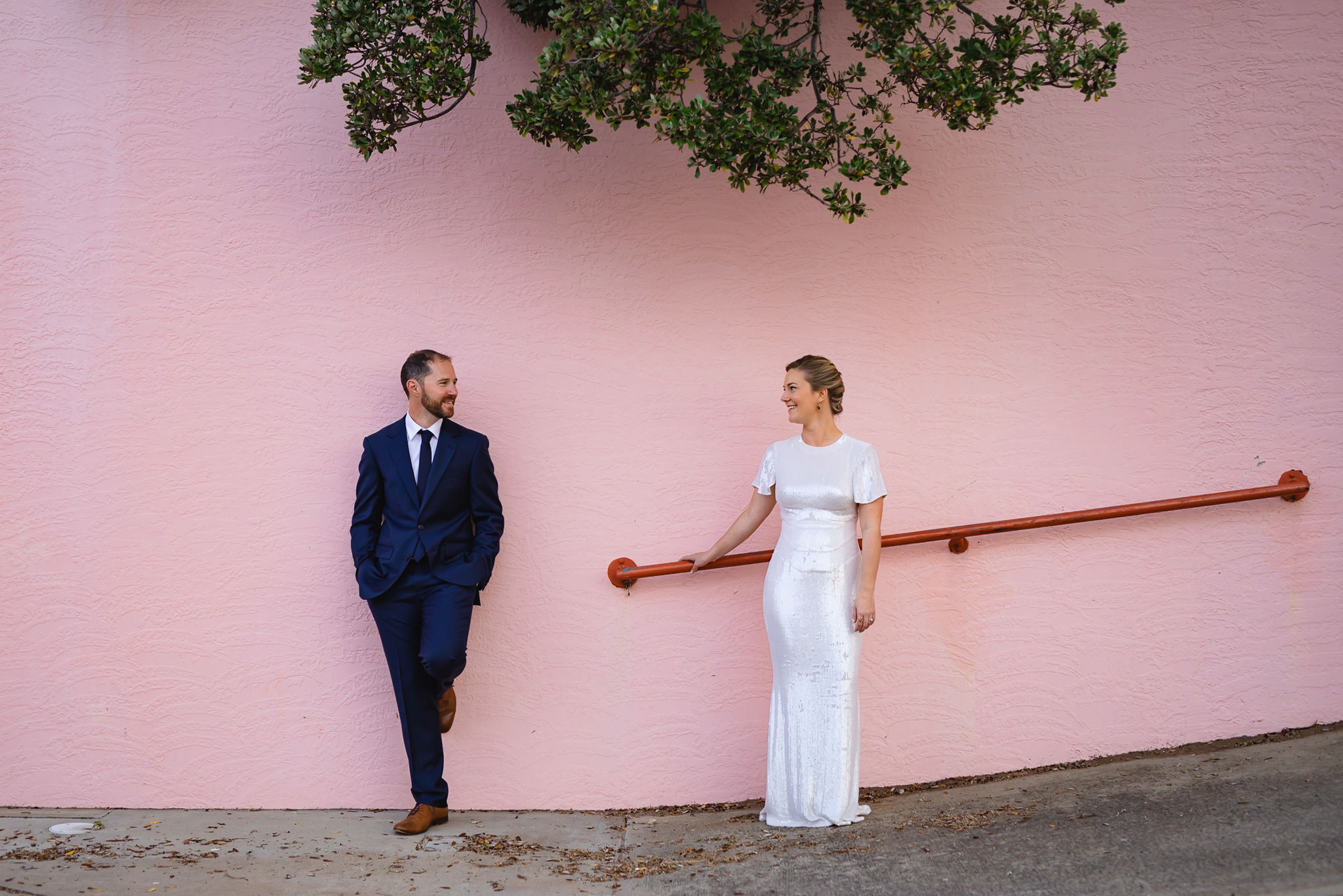 Alternative and modern bride and groom standing in front of pink wall at Bunbury Regional Art Gallery on their wedding day