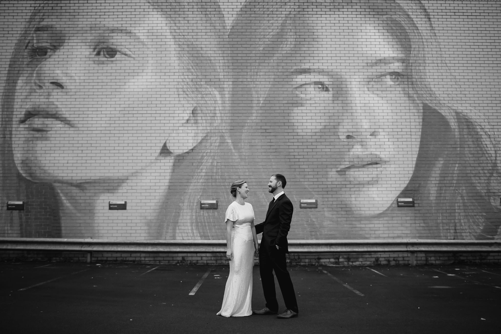 black and white photo of bride and groom on their wedding day in front of street art Rone mural in Bunbury of two girls faces behind the Westpac Bank