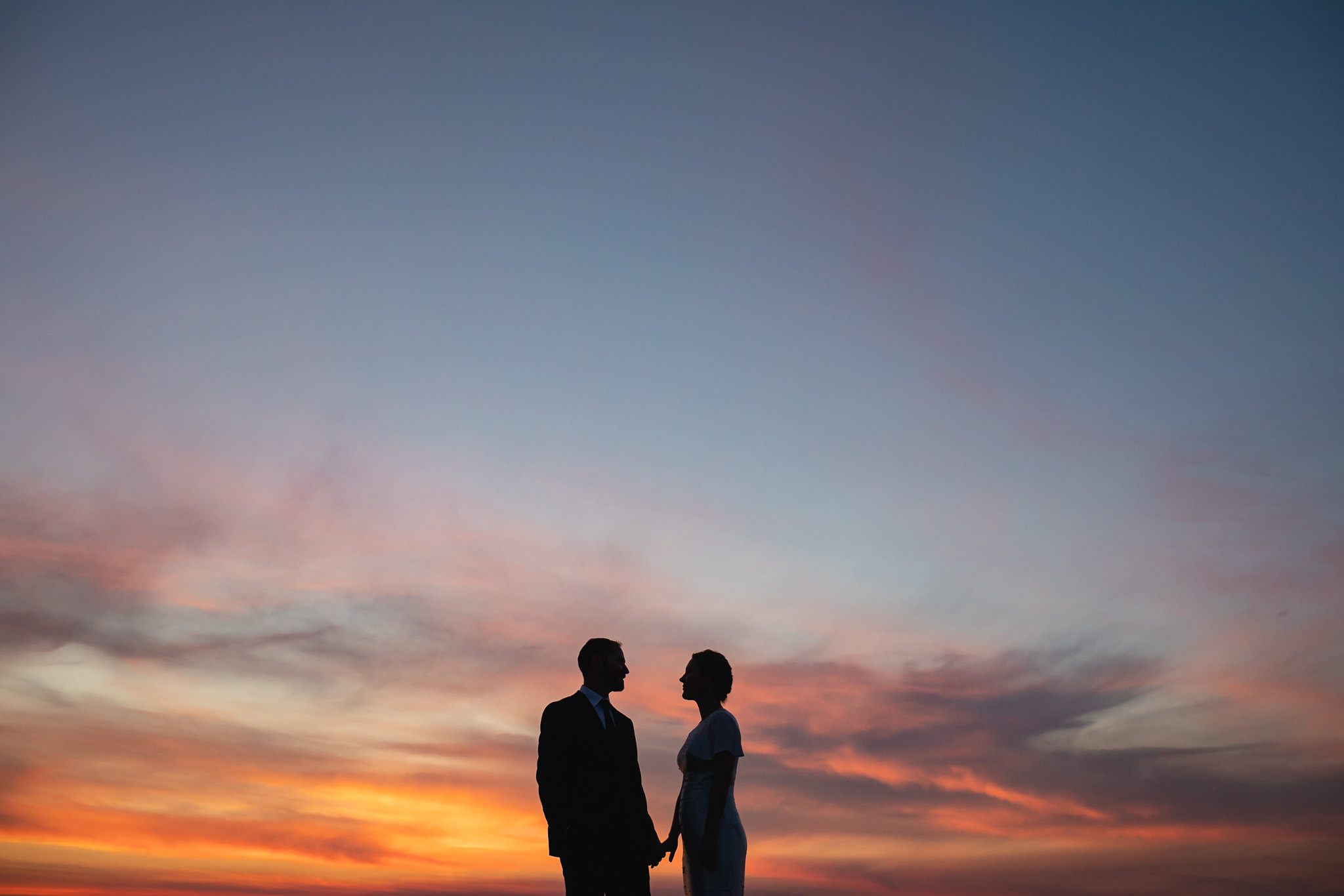 bride and groom silhouetted against red orange and pink sunset on their wedding day