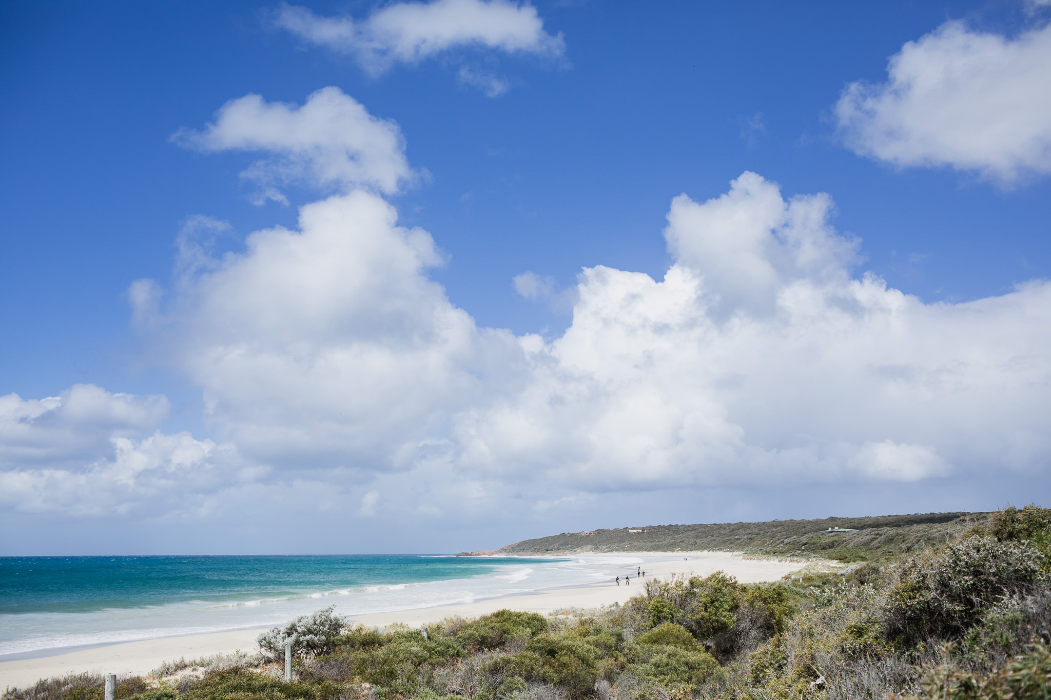 surfers walking along Bunker Bay Beach under blue sky and puffy white clouds