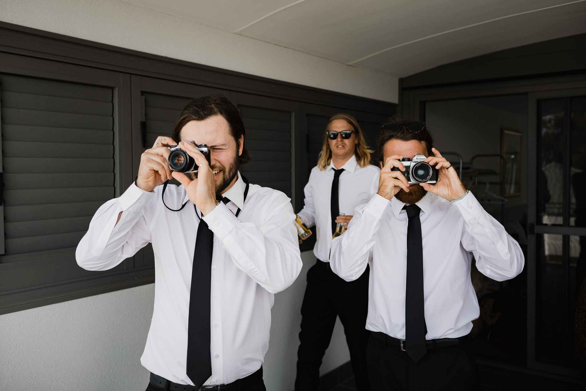 groomsmen with vintage film cameras taking photos at a wedding