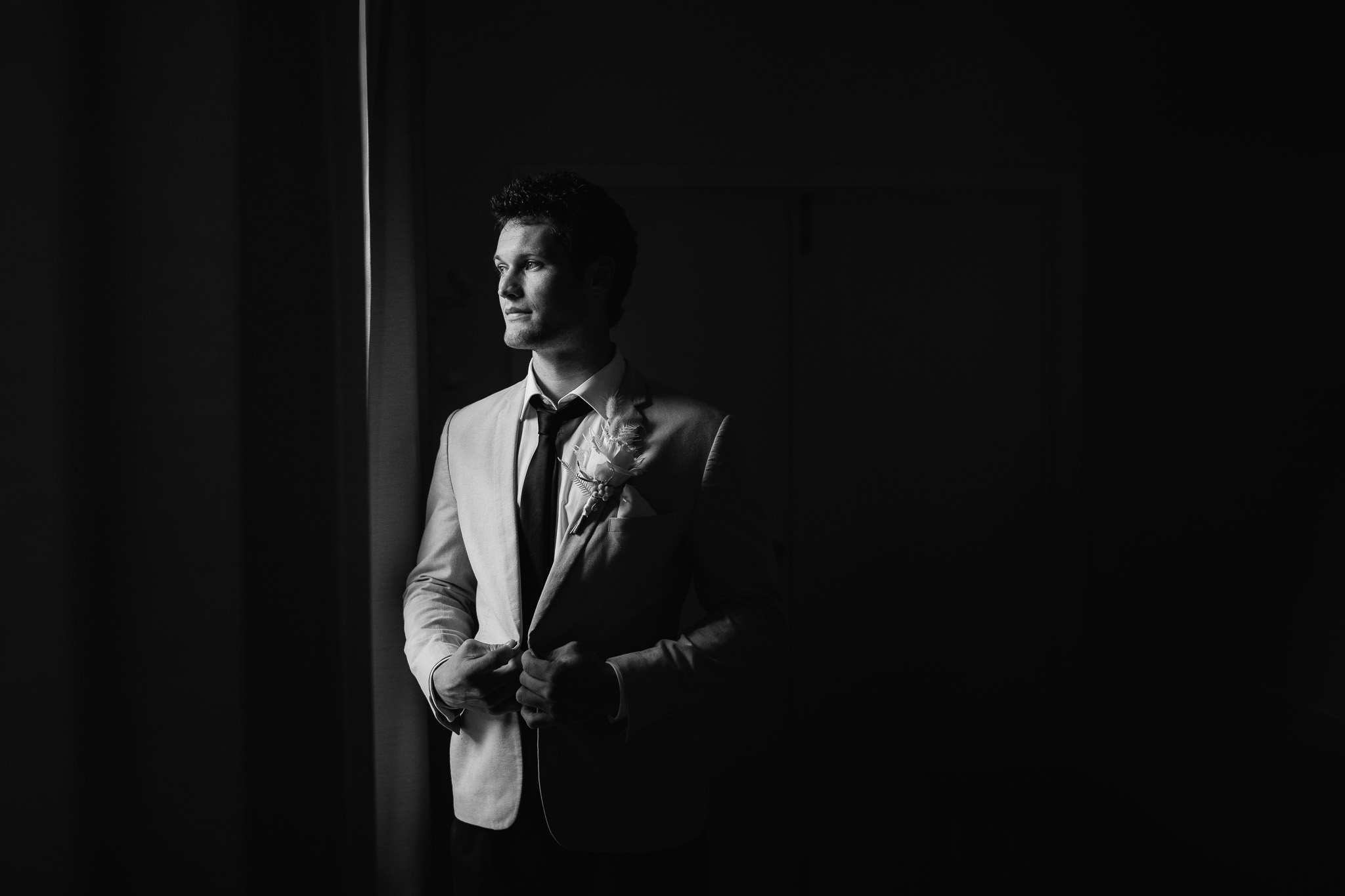 moody black and white portrait of groom just before wedding ceremony