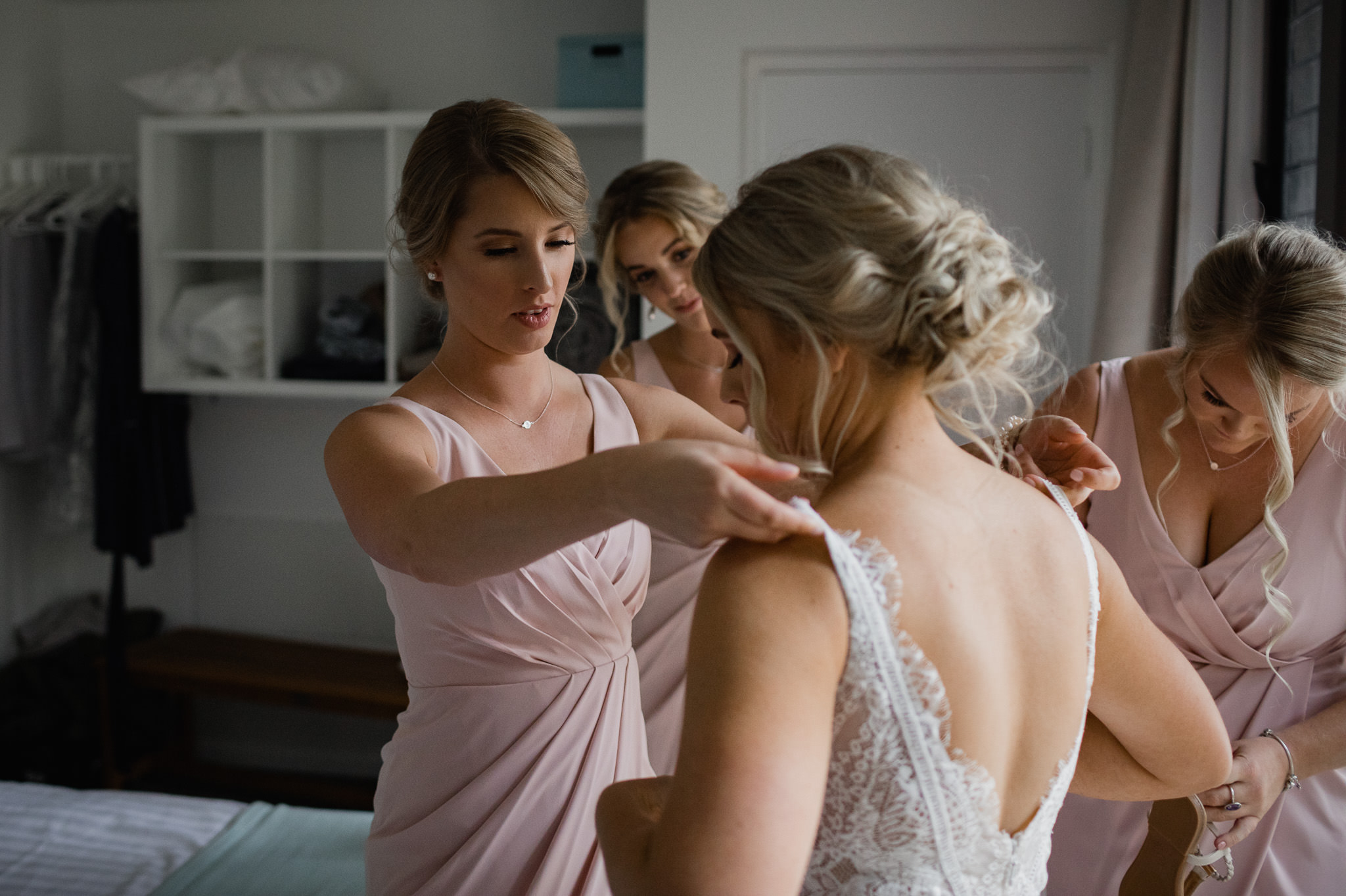 bridesmaids and sisters helping bride with wedding dress