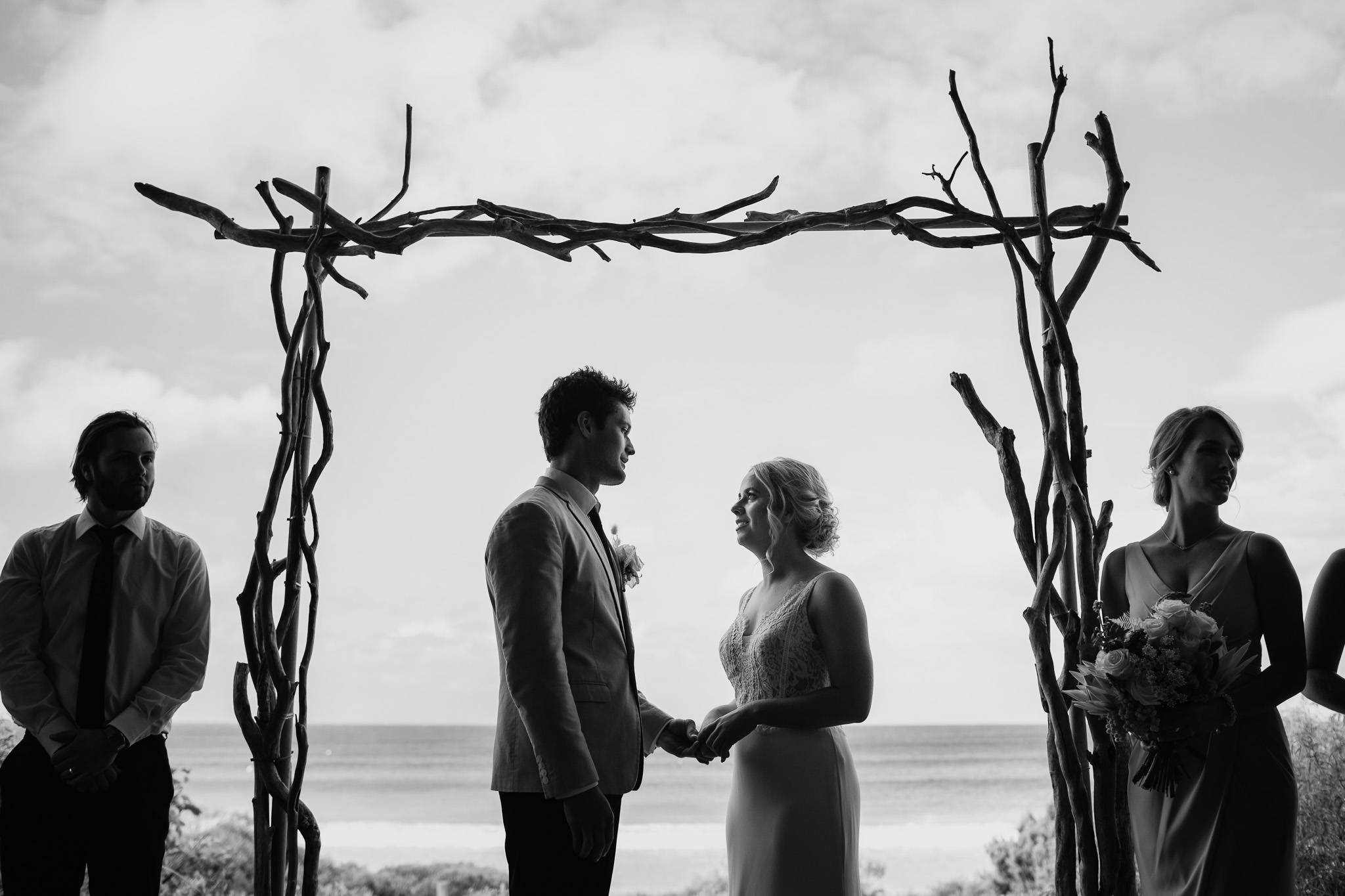 black and white photo of bride and groom standing under driftwood arbour from Ferguson Valley Events at their ceremony on Bunker Bay beach