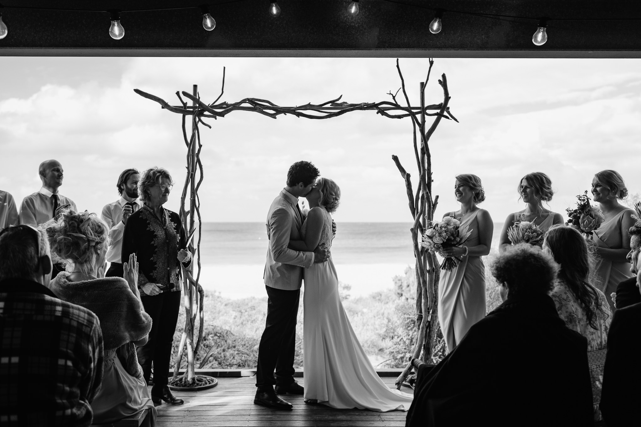 bride and groom have their first kiss under driftwood arbour from Ferguson Valley Events at their ceremony on the deck at Bunkers Beach House
