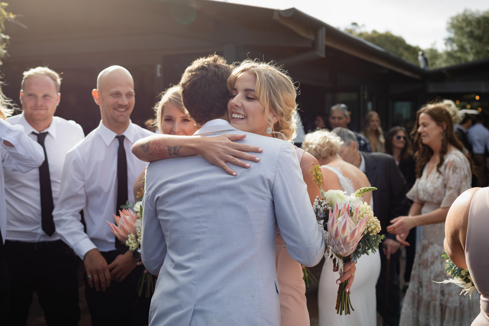 bridesmaid with tattoos and protea bouquet hugging groom after wedding