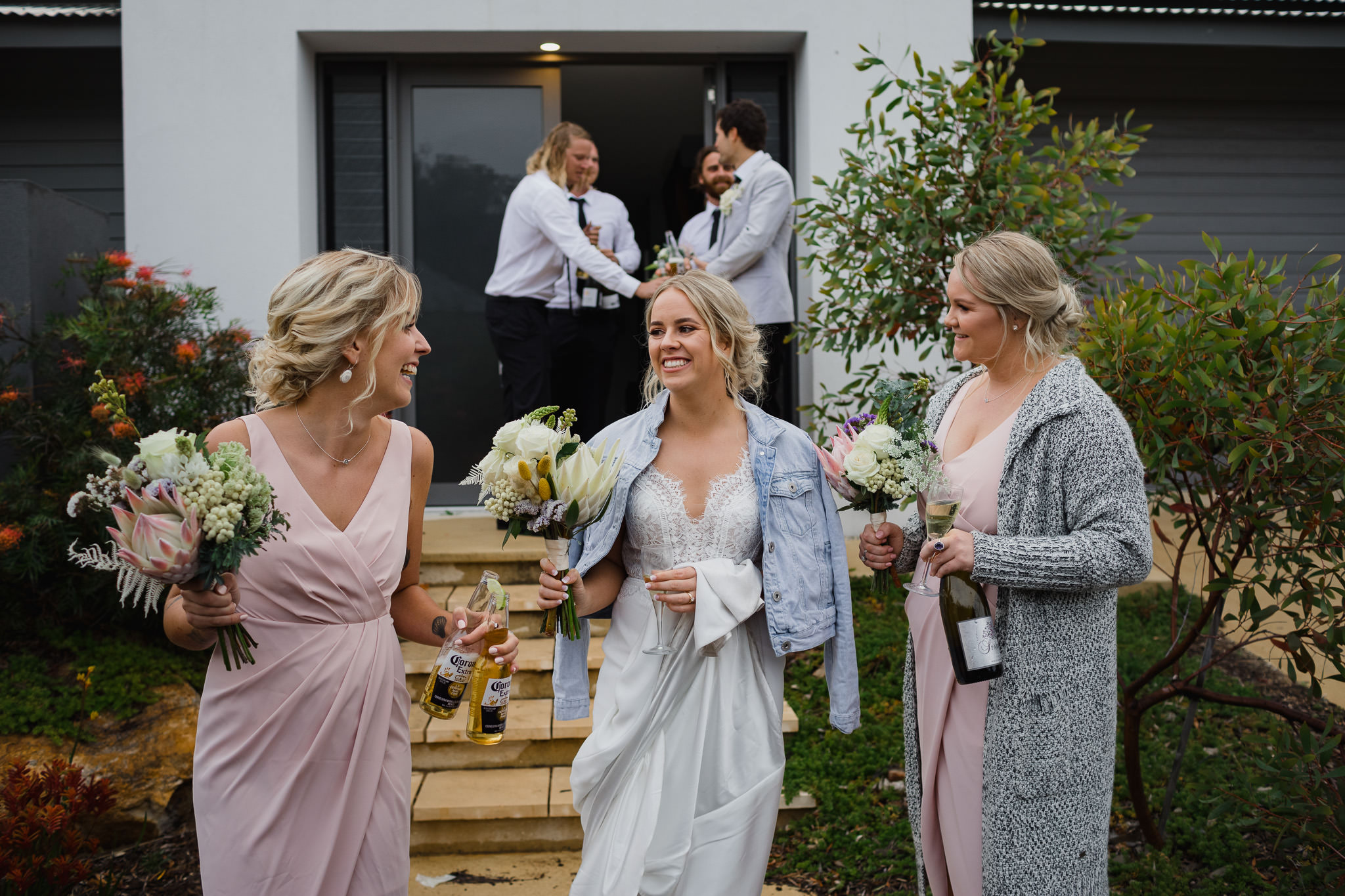 happy bride in denim jacket and laughing bridesmaids with bouquets, corona beer bottles and champagne