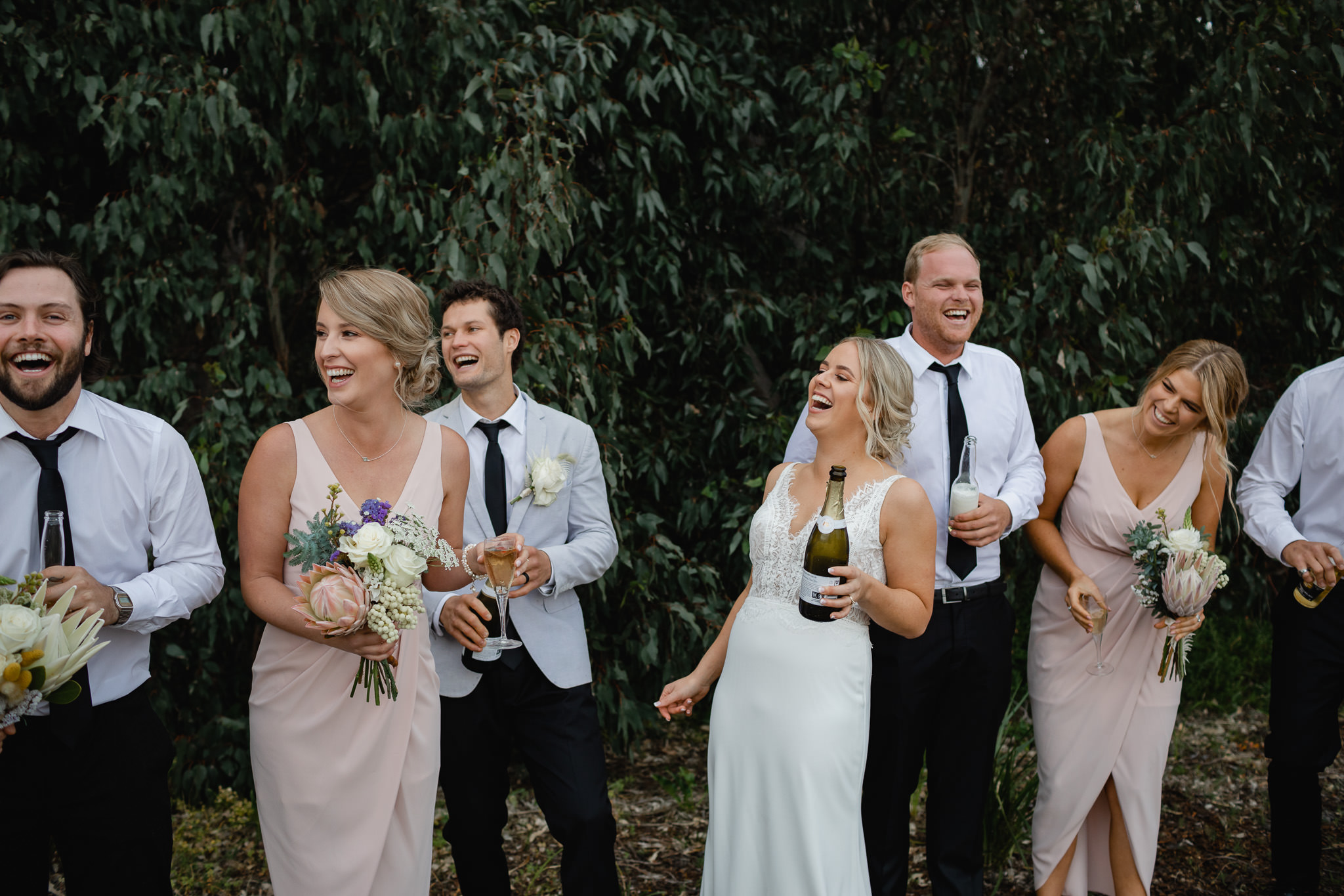 bride drinking bottle of champagne and laughing with bridal party