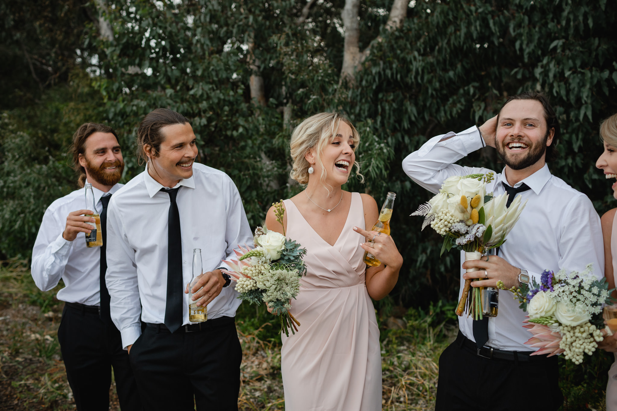 bridesmaids and groomsmen drinking beer and laughing during bridal party photo session