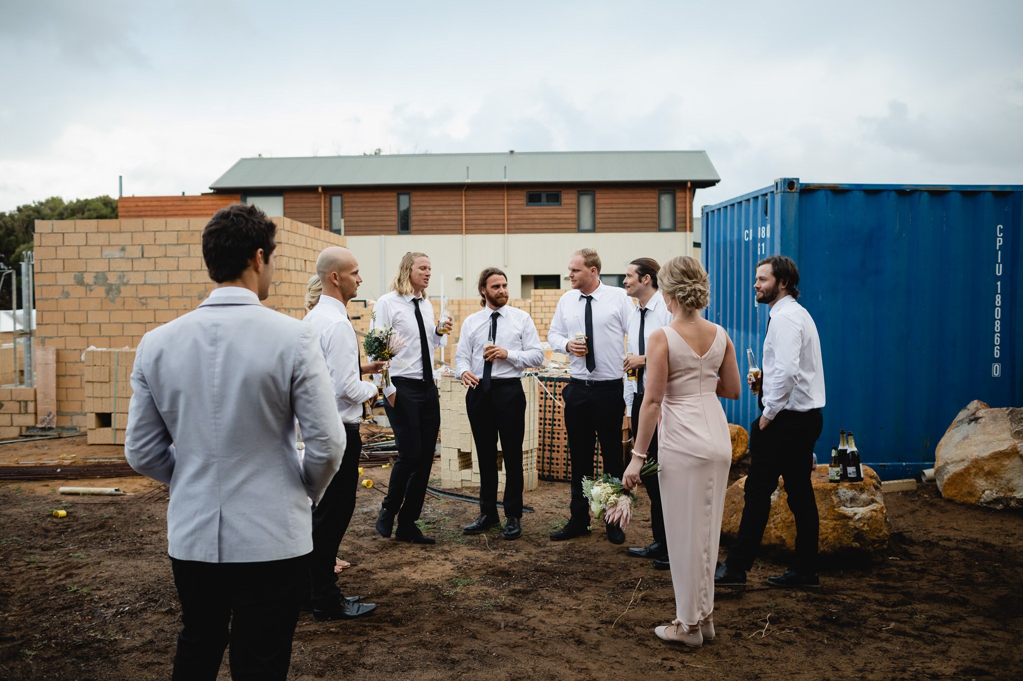 groomsmen and bridesmaids hanging out at building site with blue sea container
