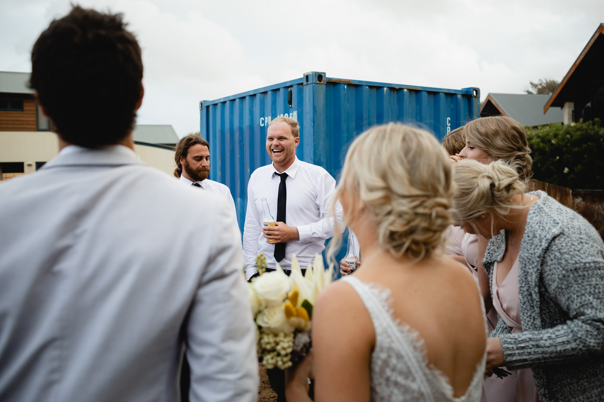 groomsman laughing while hanging out at building site with a blue sea container