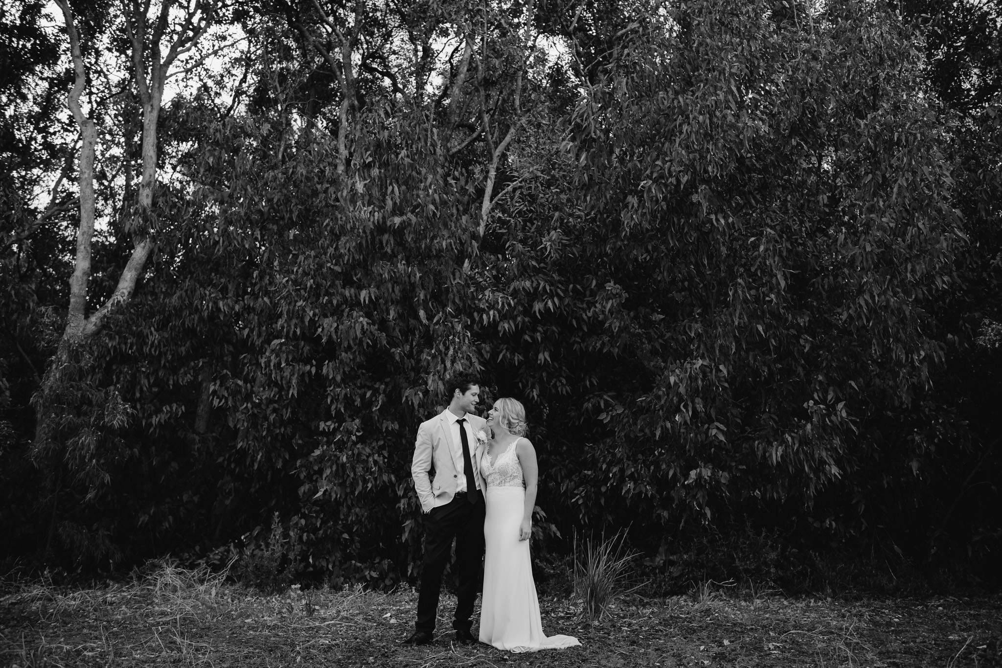 black and white photo of bride and groom against dark trees at Bunker Bay beach