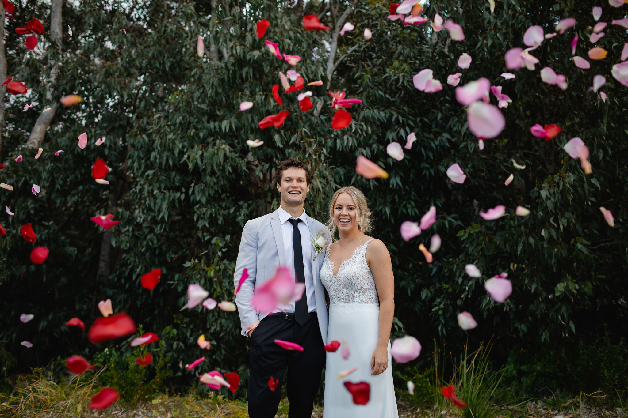 bride and groom laughing and looking at camera while being showered in red and pink rose petals