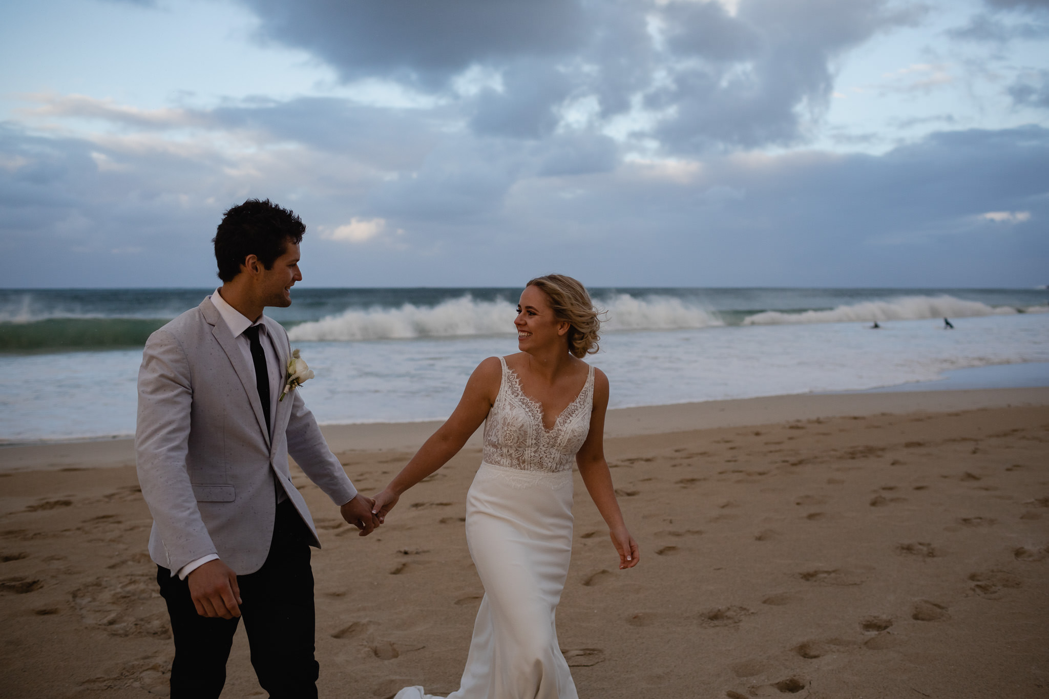 bride and groom walking along Bunker Bay beach at sunset