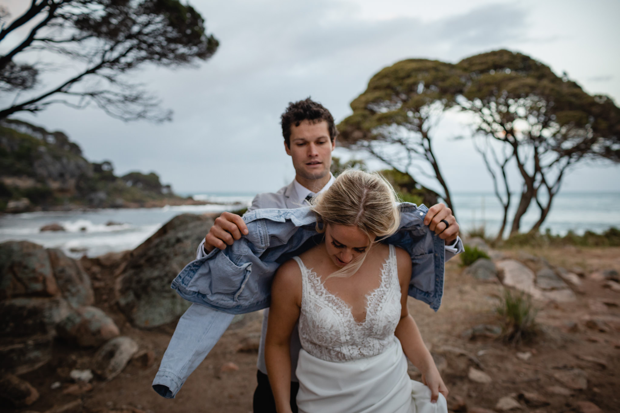 considerate husband placing denim jacket on wife's shoulders at Shelley Cove after their wedding