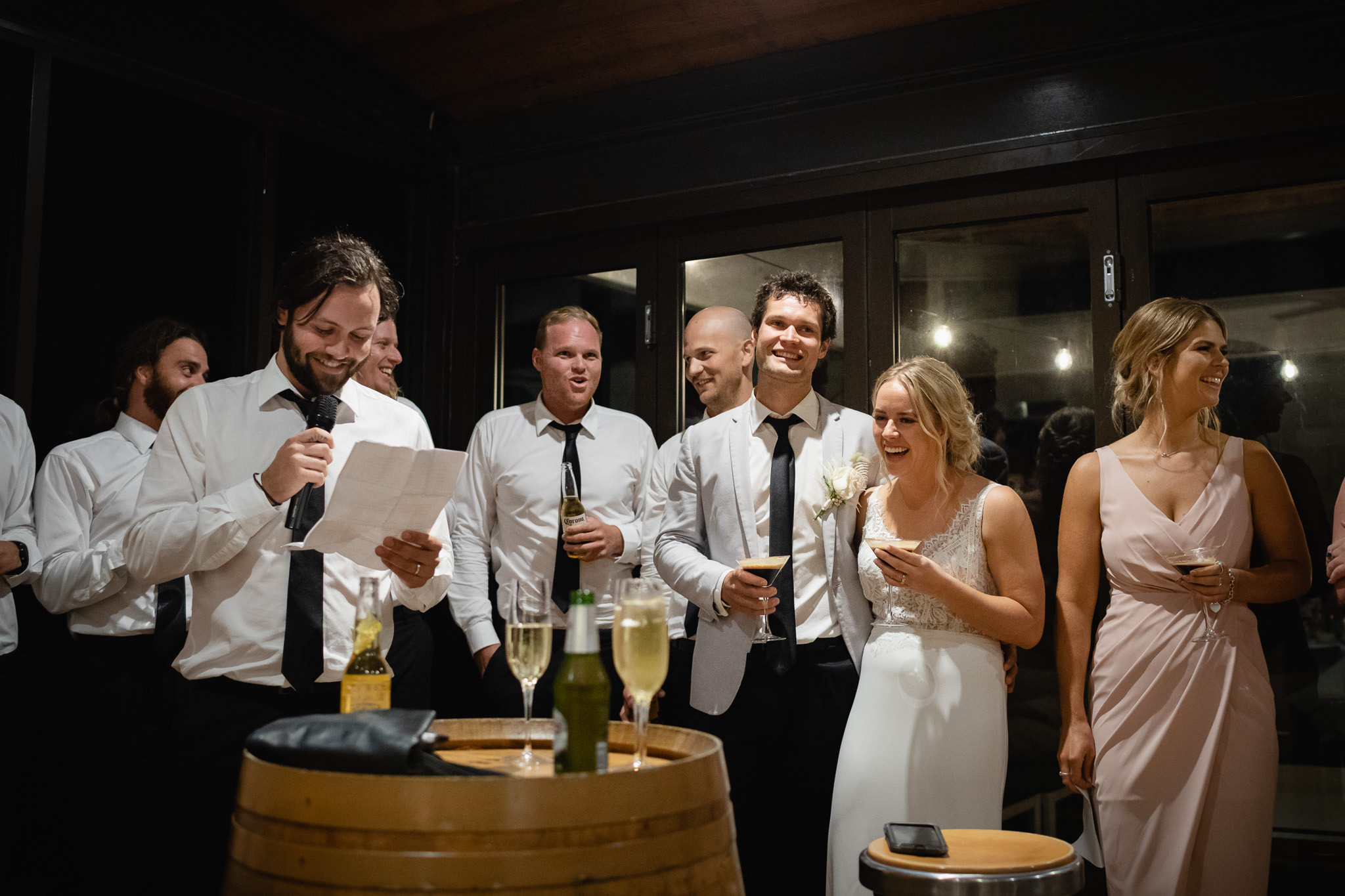 bride and groom laughing while groomsman gives speech at their wedding