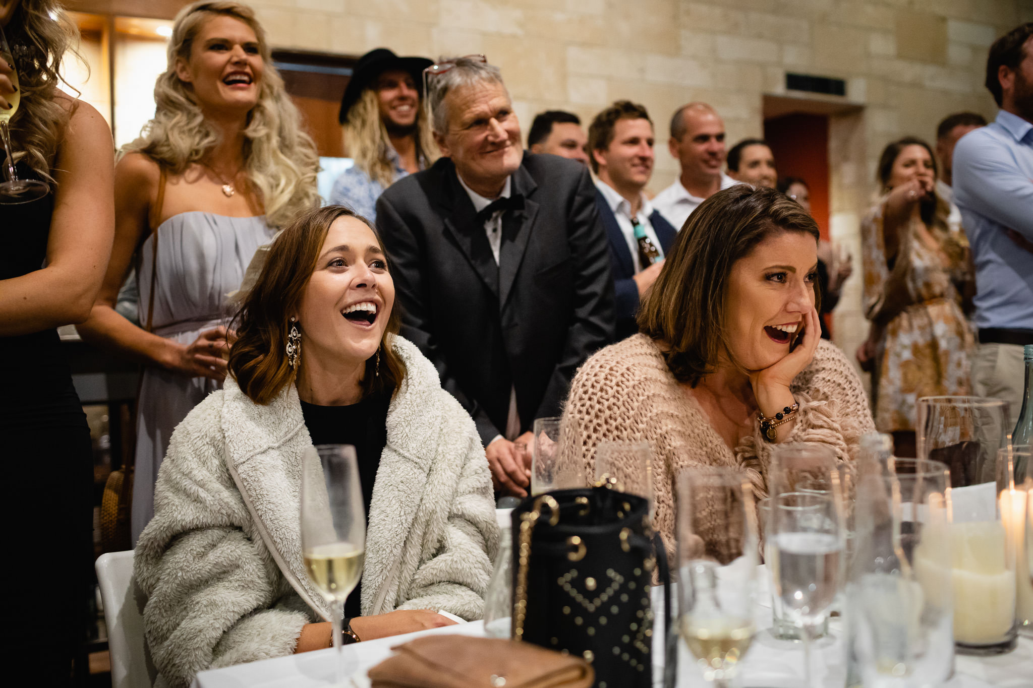 guests with glasses of champagne laughing during speeches at wedding reception at Bunker Bay cafe