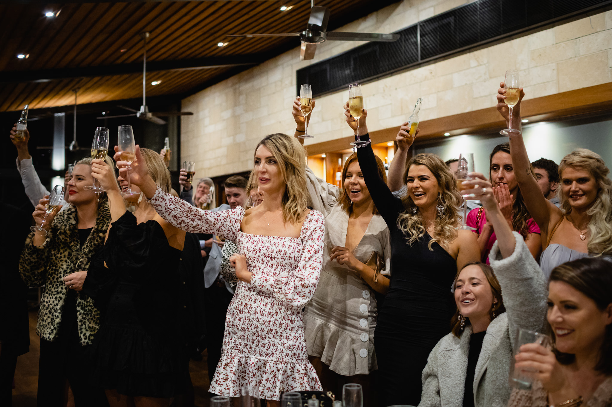 guests raising champagne glasses in the air to toast wedding speeches at Bunkers Beach House