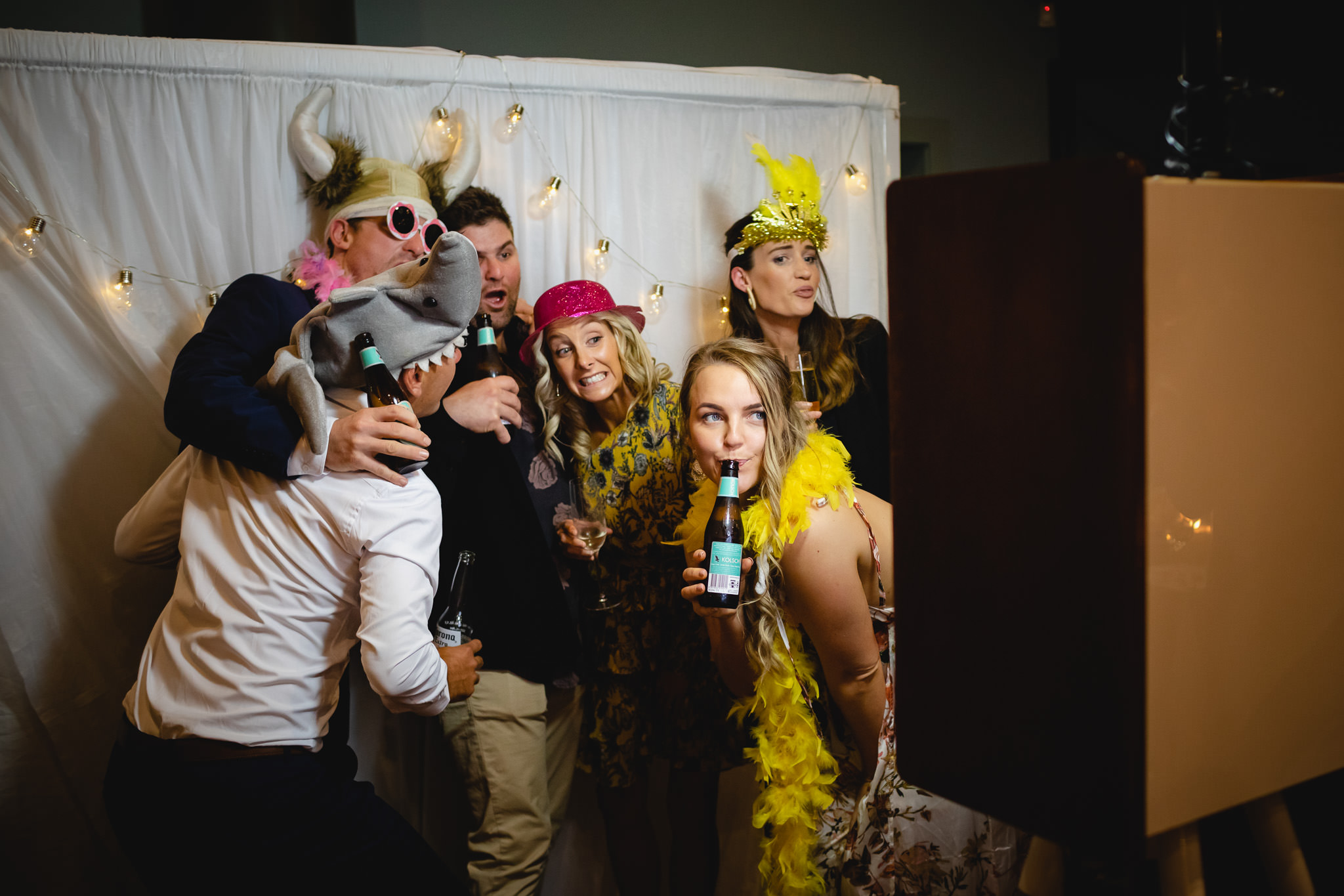 guests posing with feather boas and party hats in front of photo booth at Dunsborough wedding