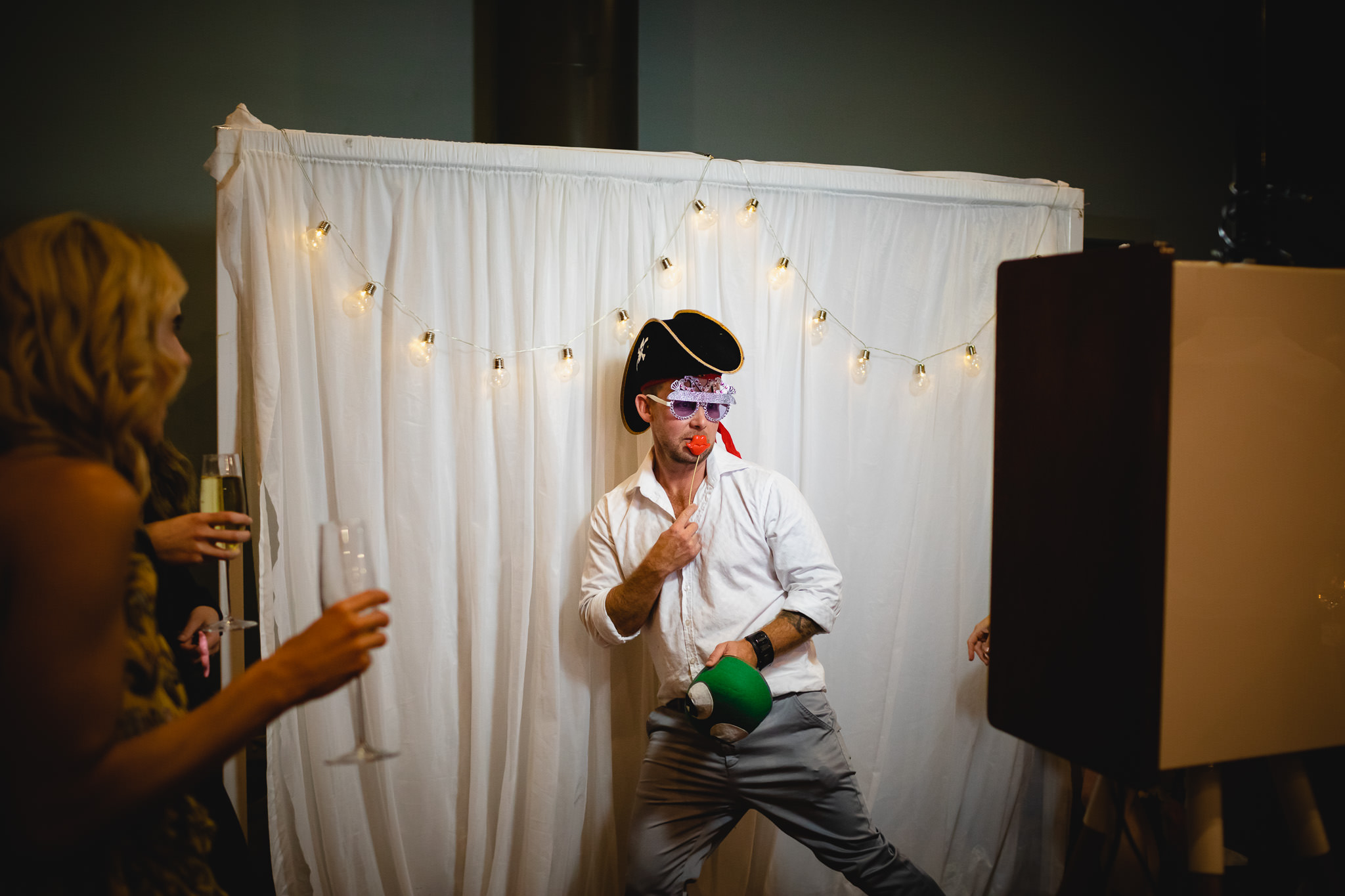 guest with pirate costume posing in front of photo booth at a wedding