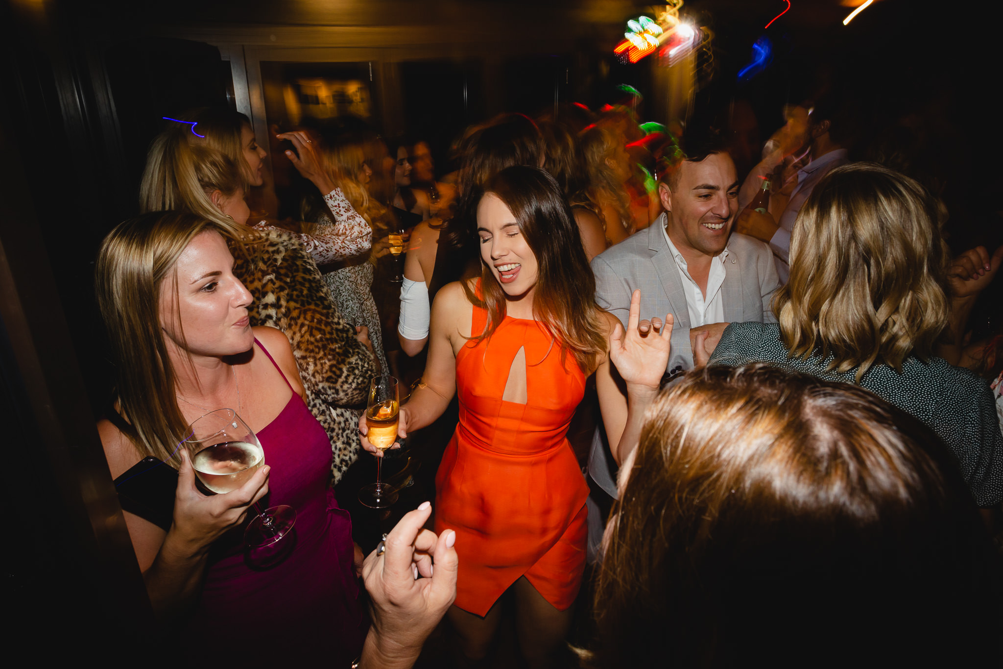 girl in orange dress and guests partying on dance floor at Bunker Bay wedding