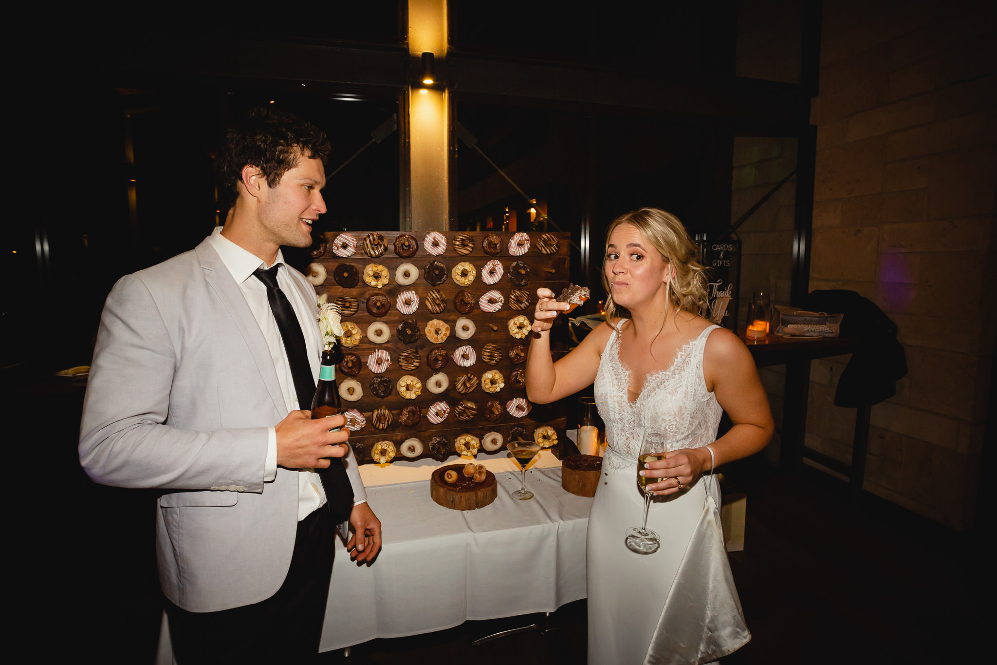 bride and groom eating donuts from donut wall at Bunkers Beach House