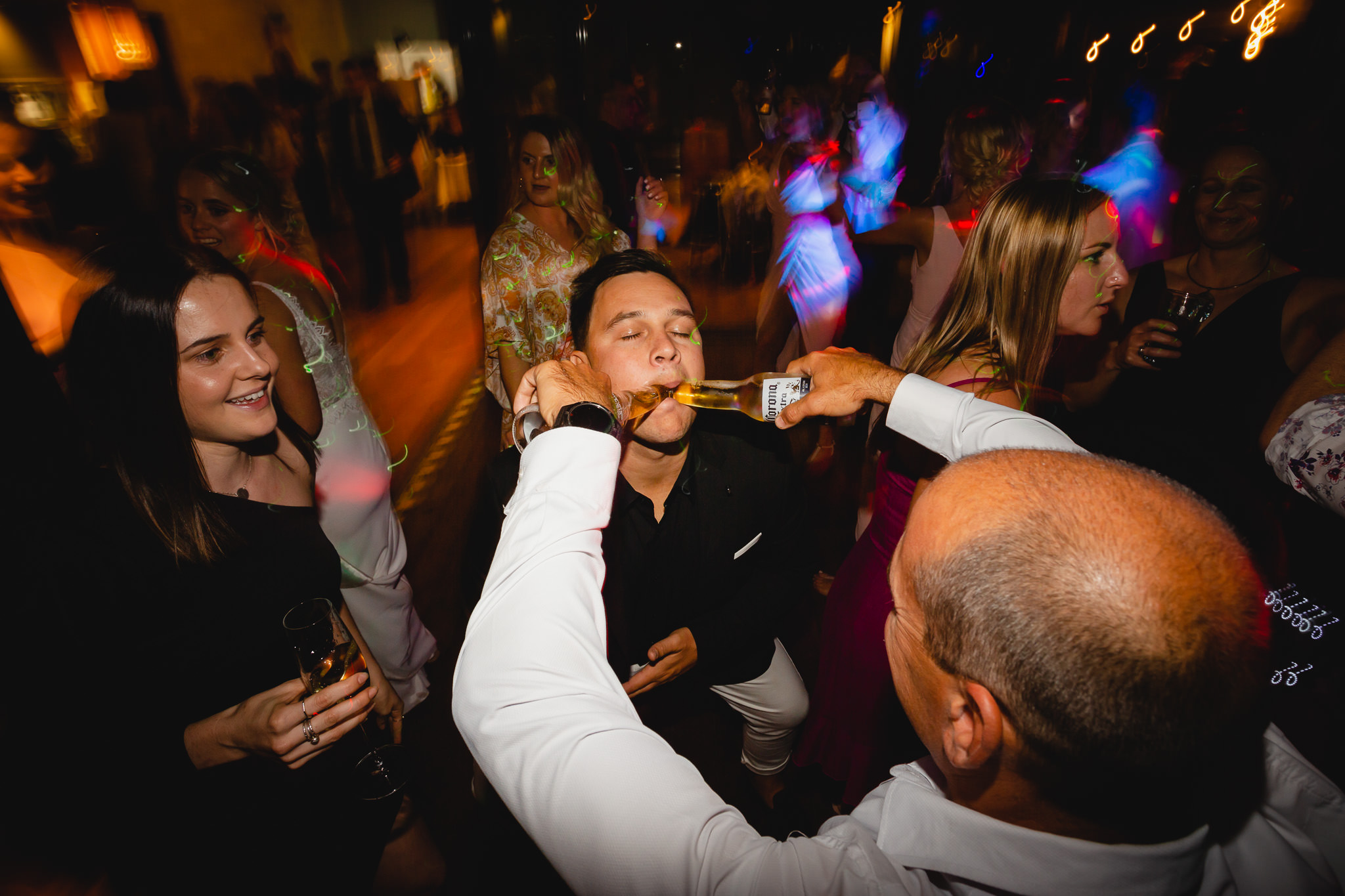 wedding guest pouring two corona beers into friends mouth on dance floor at a wedding at Bunkers Beach House
