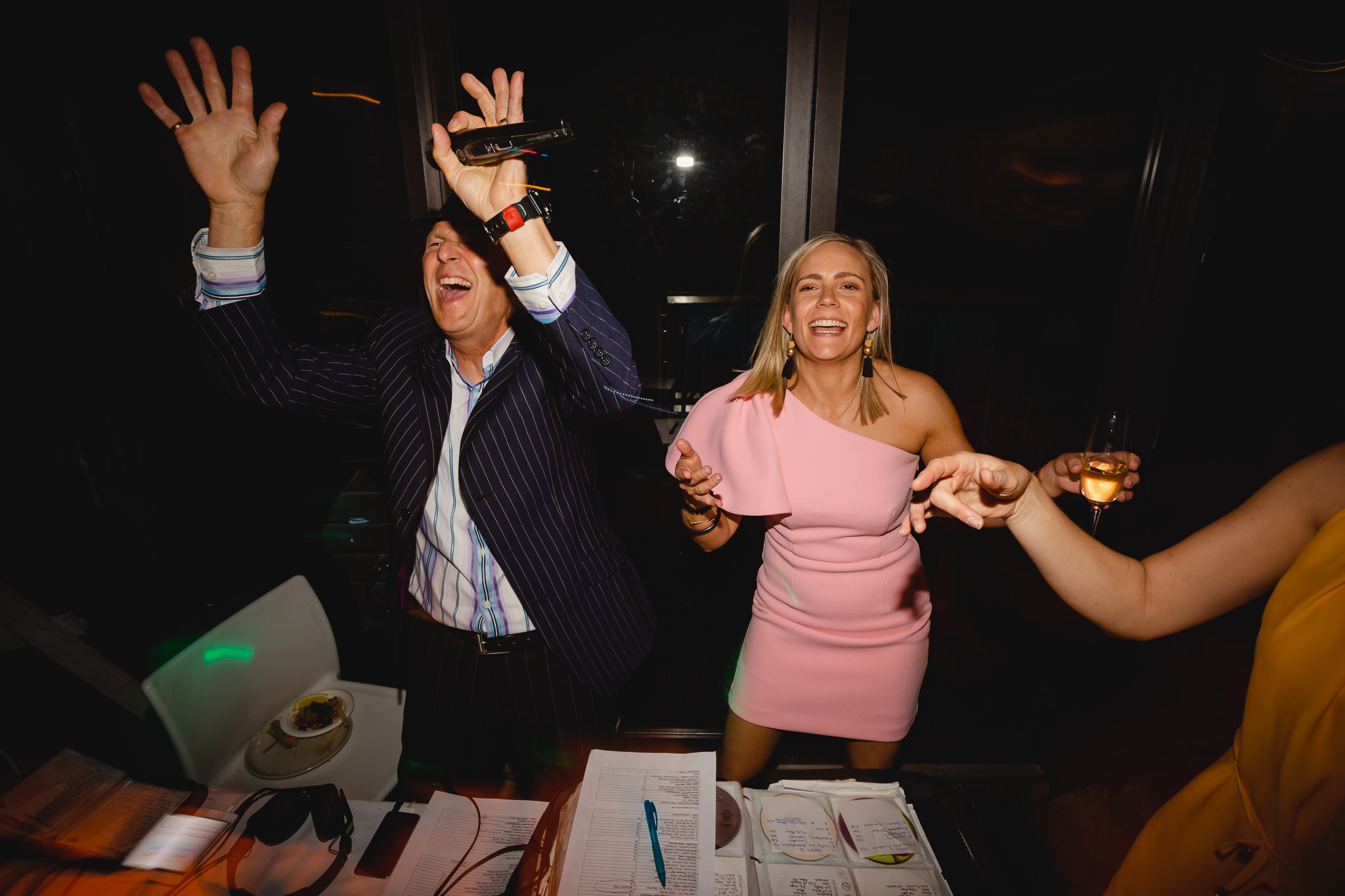 DJ Macca dancing with woman in pink dress while playing music at wedding reception