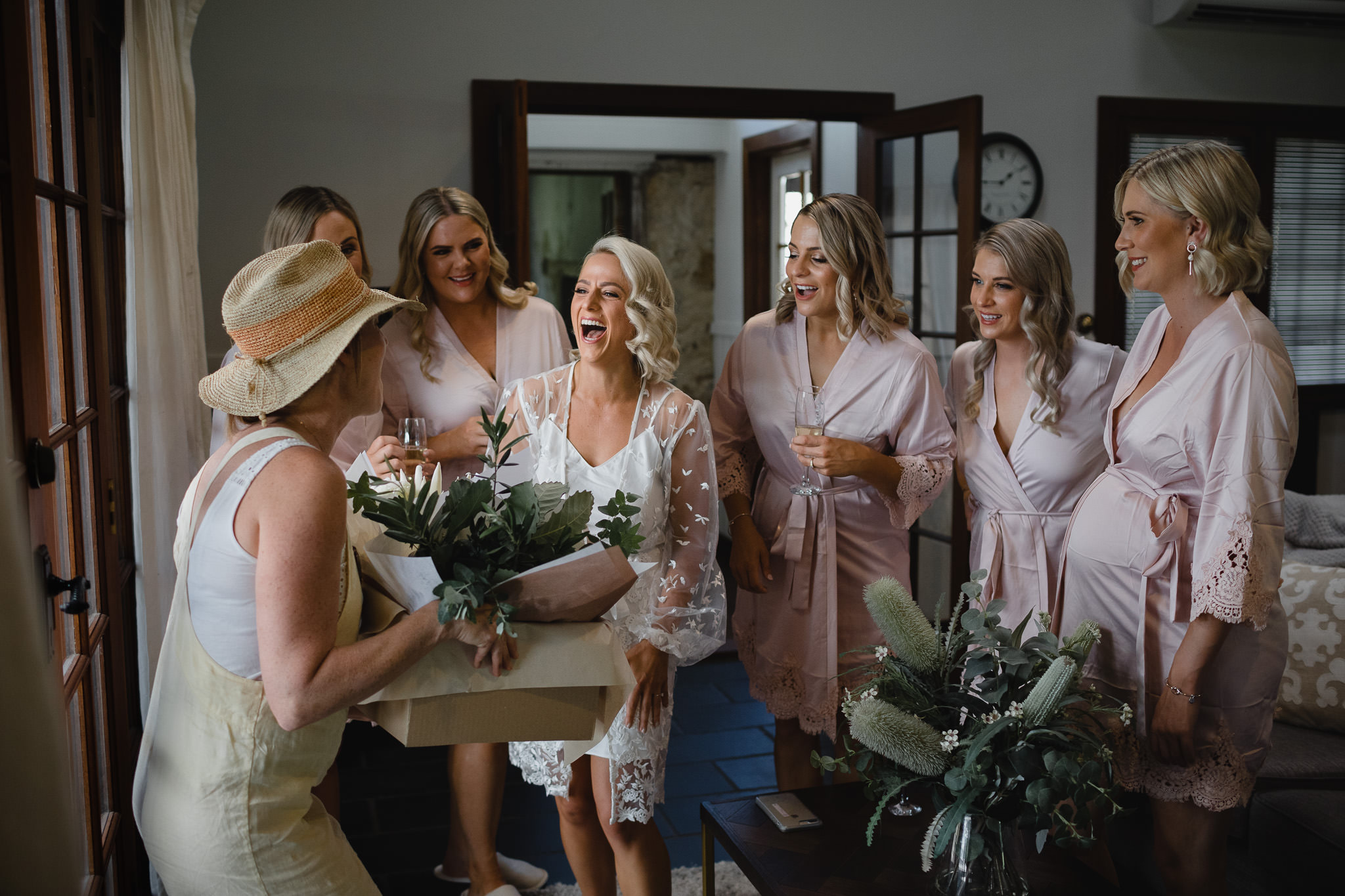 bride and bridesmaids greeting florist delivering flowers at a wedding