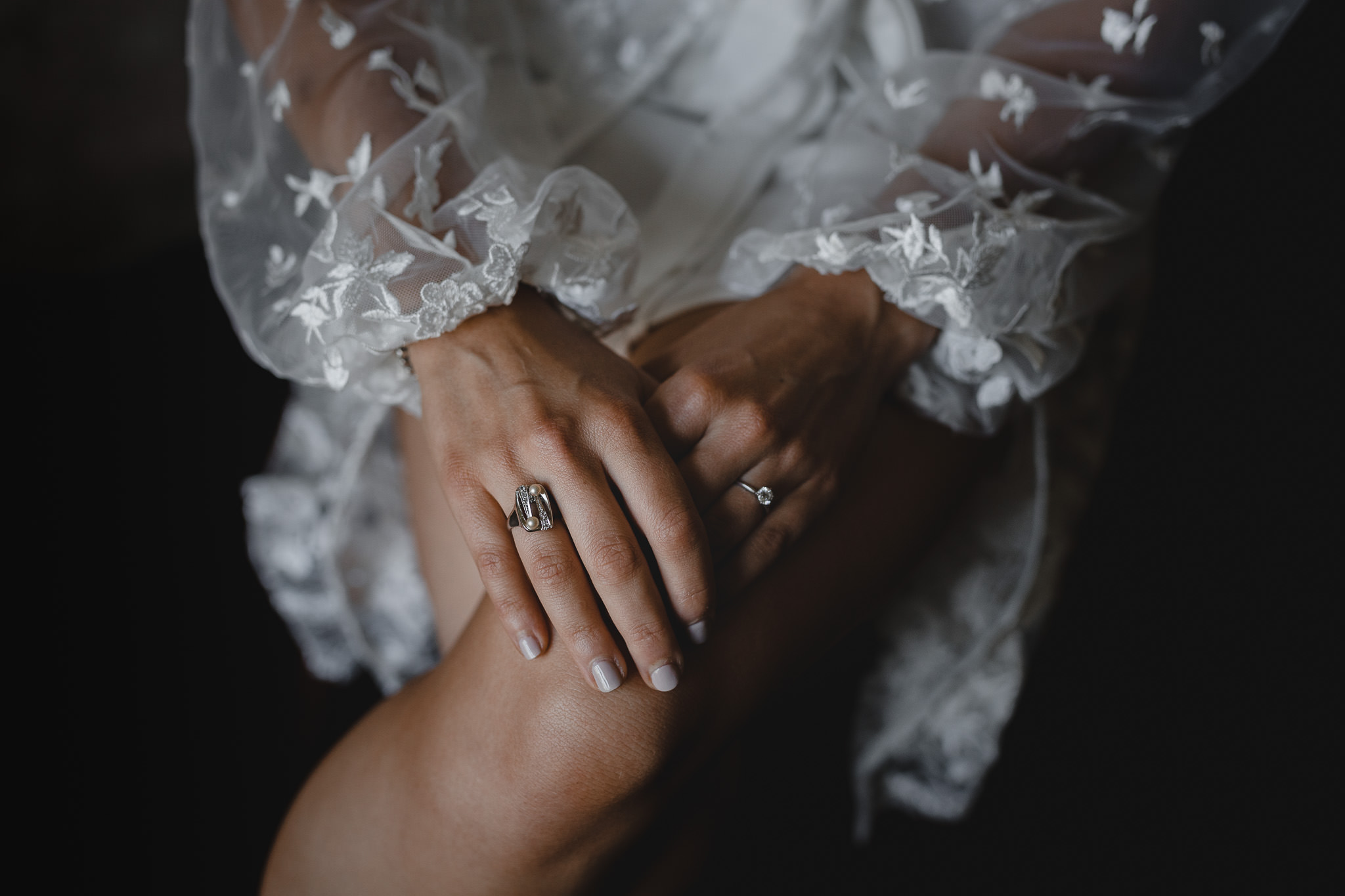 bride with vintage pearl engagement ring from grandmother, and diamond engagement ring