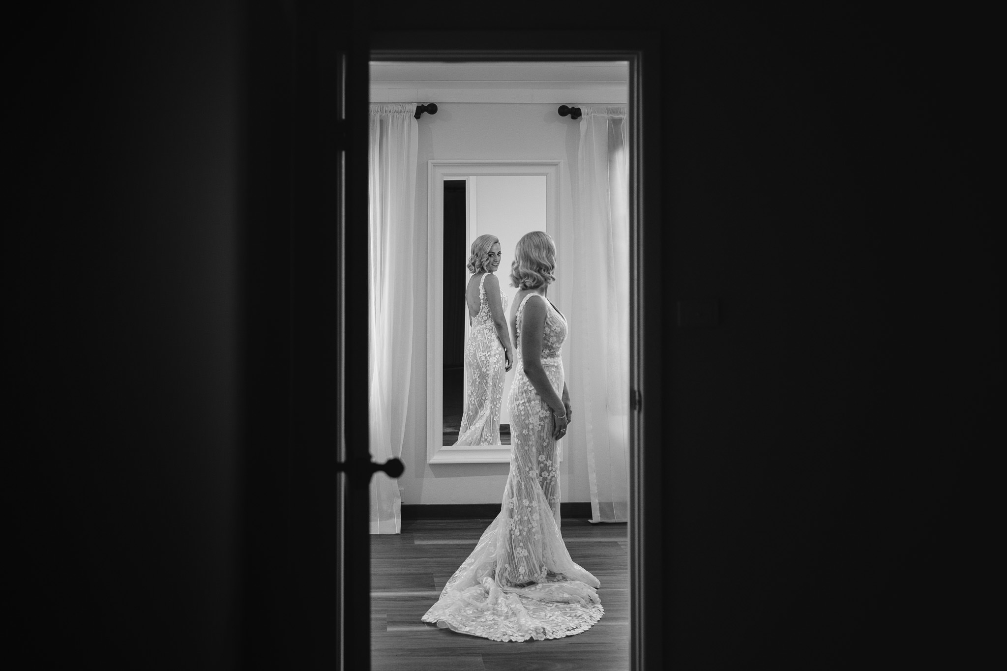 bride in Wedding Societe wedding dress by Bridal by Aubrey Rose checking herself out in mirror before ceremony