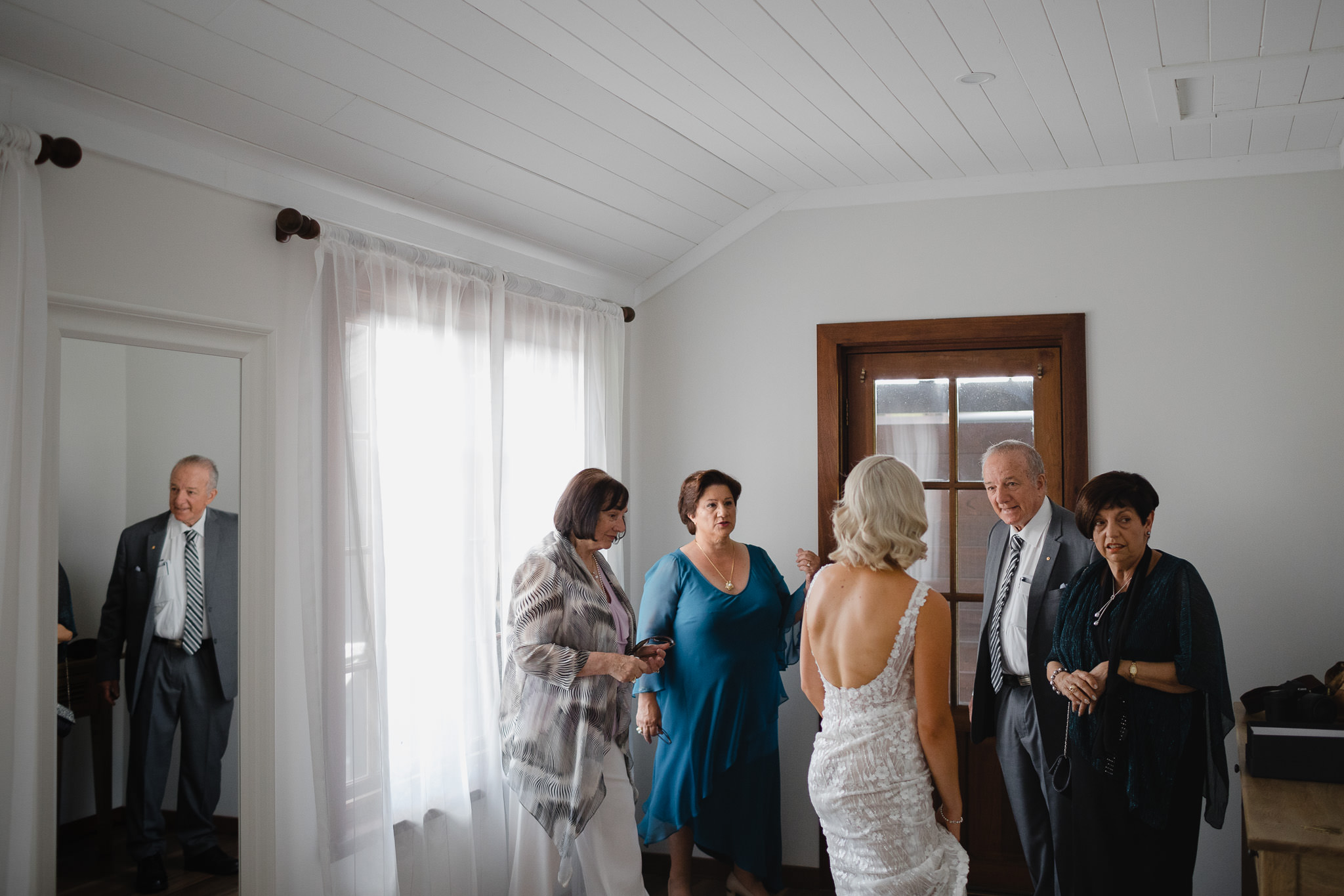 mum and grandparents greeting bride before ceremony, grandfather reflected in the mirror