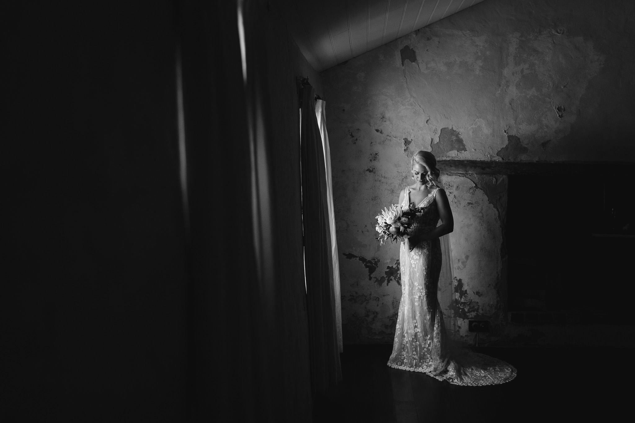 bride in wedding societe dress by Bridal by Aubrey Rose with wedding bouquet in dark old cottage room at Old Broadwater Farm before ceremony