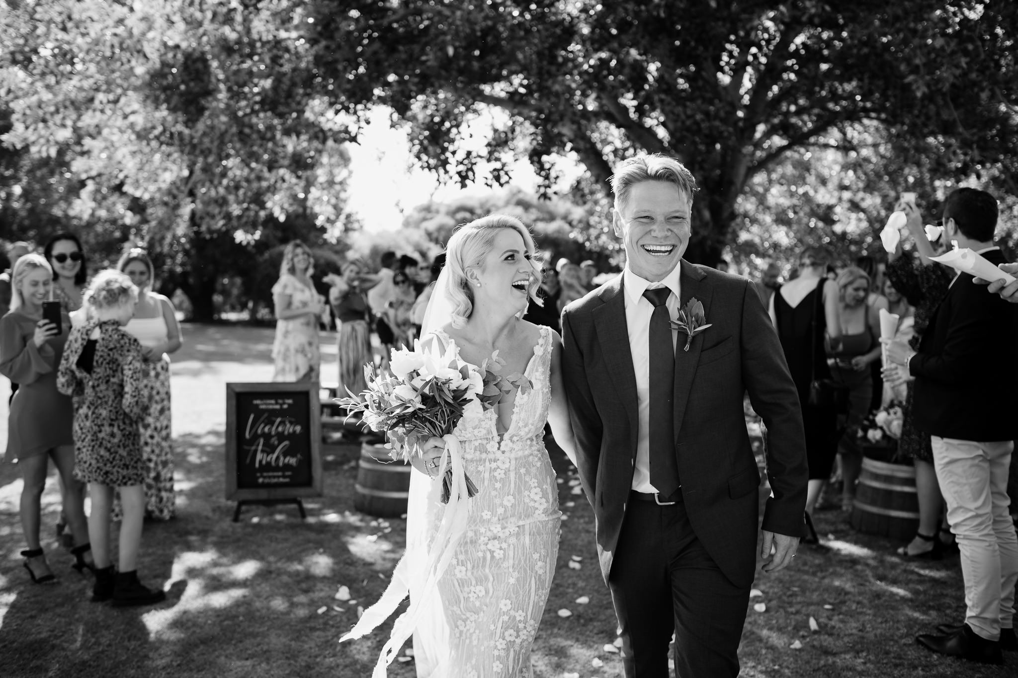 Black and white photo of bride and groom laughing as they walk back up the aisle at the wedding at Old Broadwater Farm in Busselton